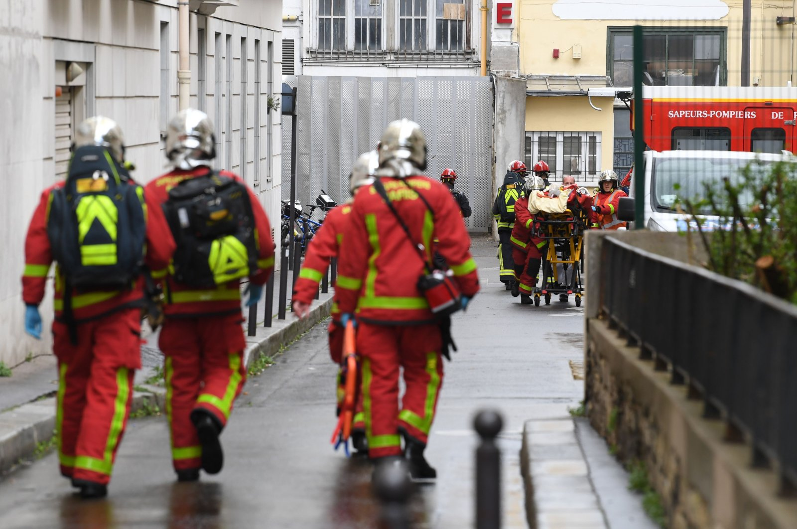 French firefighters move an injured person into an ambulance near the former offices of the French satirical magazine Charlie Hebdo, Paris, France, Sept. 25, 2020. (AFP Photo)