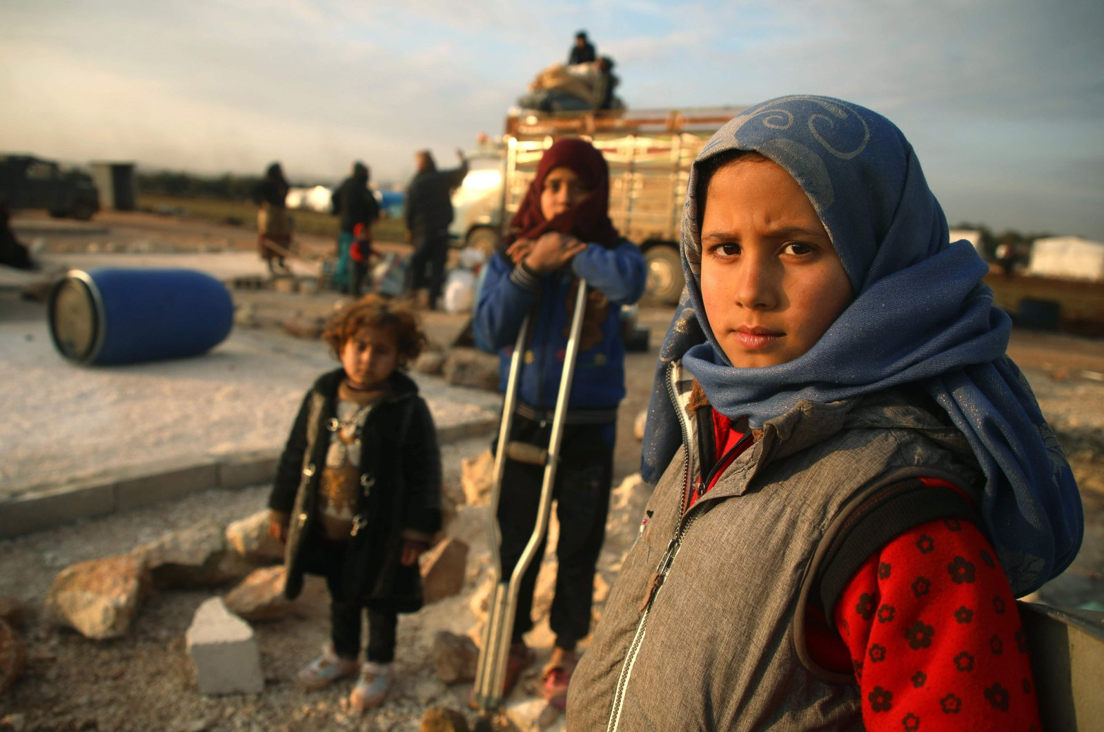 Syrian children pose for a picture as their families prepare to flee a camp for the displaced, east of Sarmada in the north of northwestern Idlib province, Syria, Feb. 16, 2020. (AFP Photo)