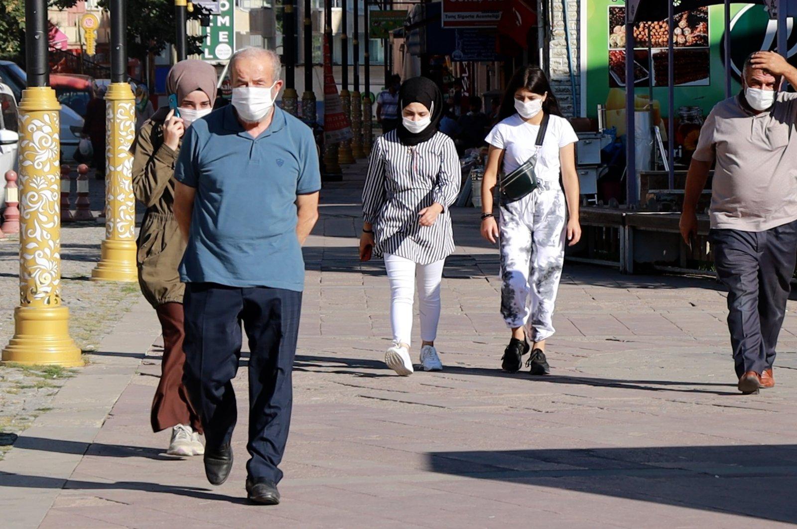 People wearing protective masks walk on a street in Gümüşhane, northern Turkey, Sept. 24, 2020. (IHA Photo)