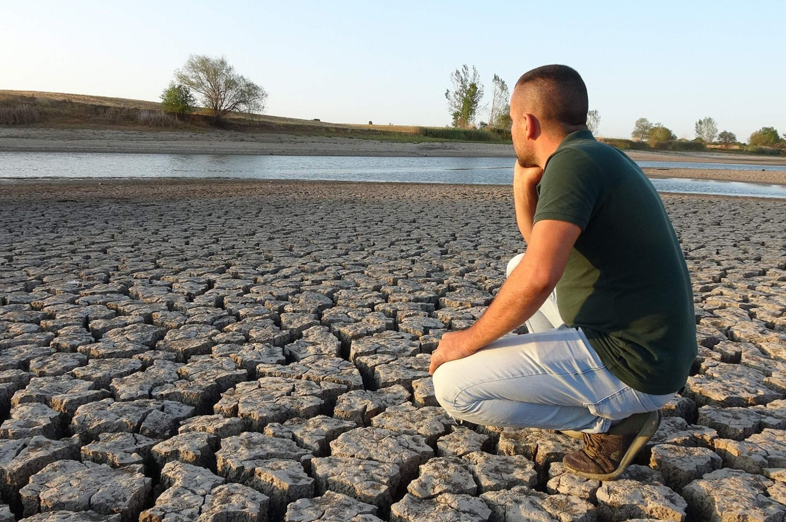 A man looks at the dry land next to a depleted pond, in Edirne, Turkey, Sept. 25, 2020. (DHA Photo)