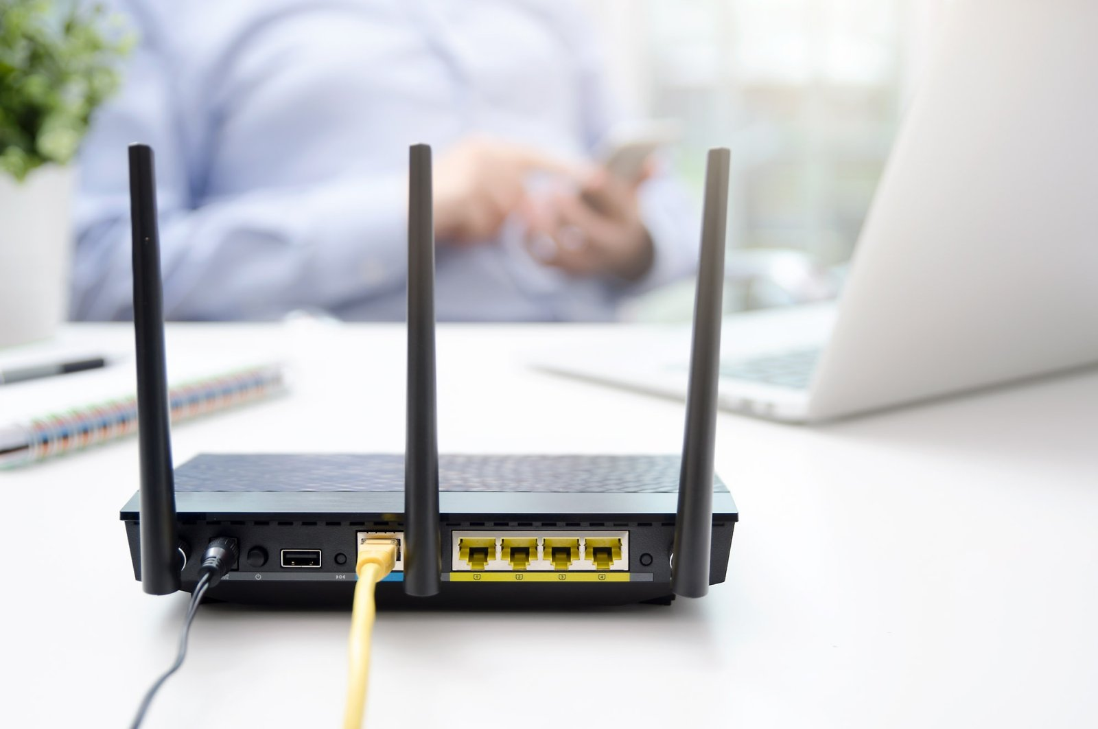 A wireless router seen as a man uses a smartphone in the background. (Shutterstock Photo)