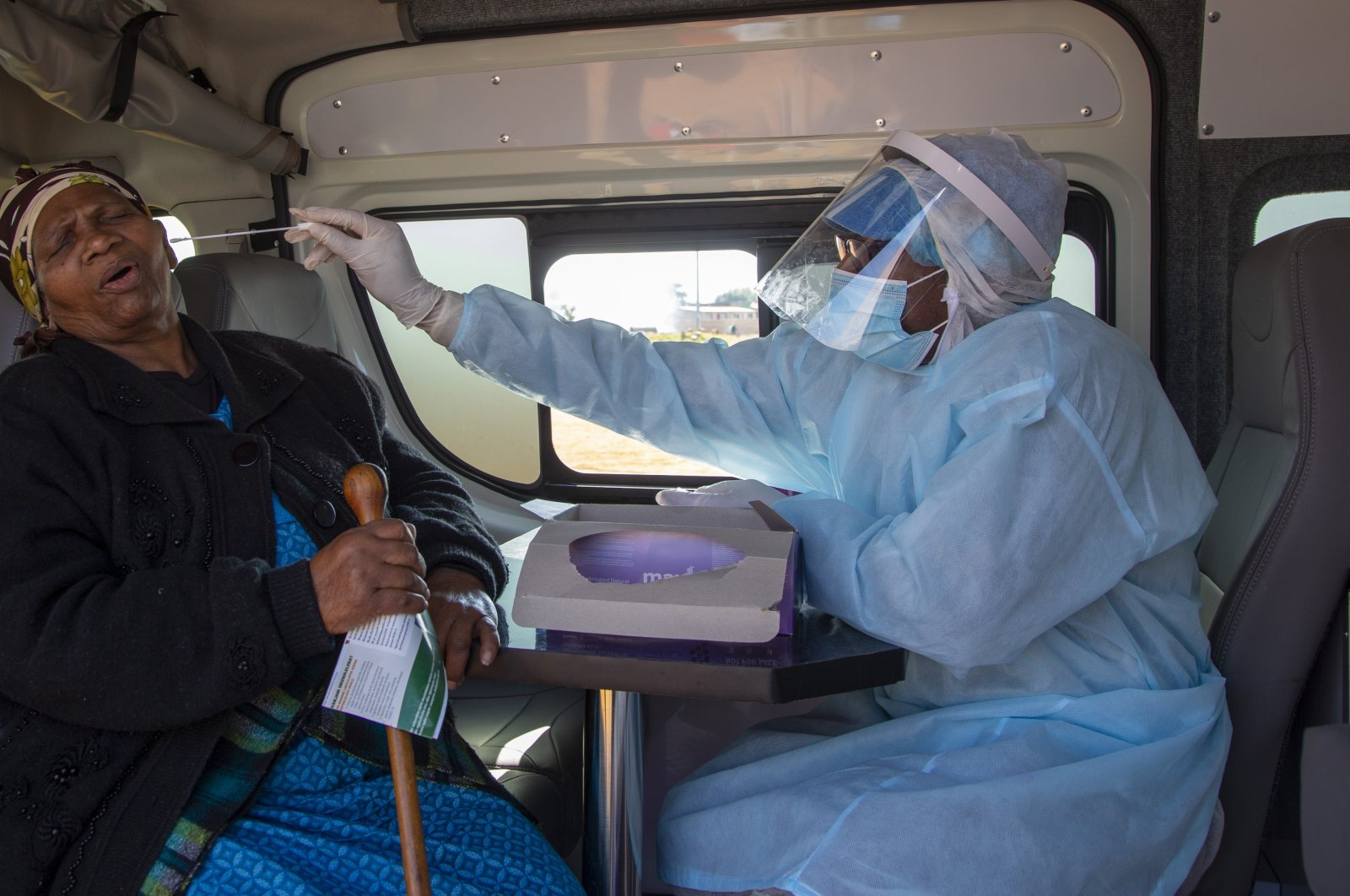 An elderly woman reacts as a health worker collects a sample for a COVID-19 test, near Johannesburg, South Africa, May 22, 2020. (AP Photo)