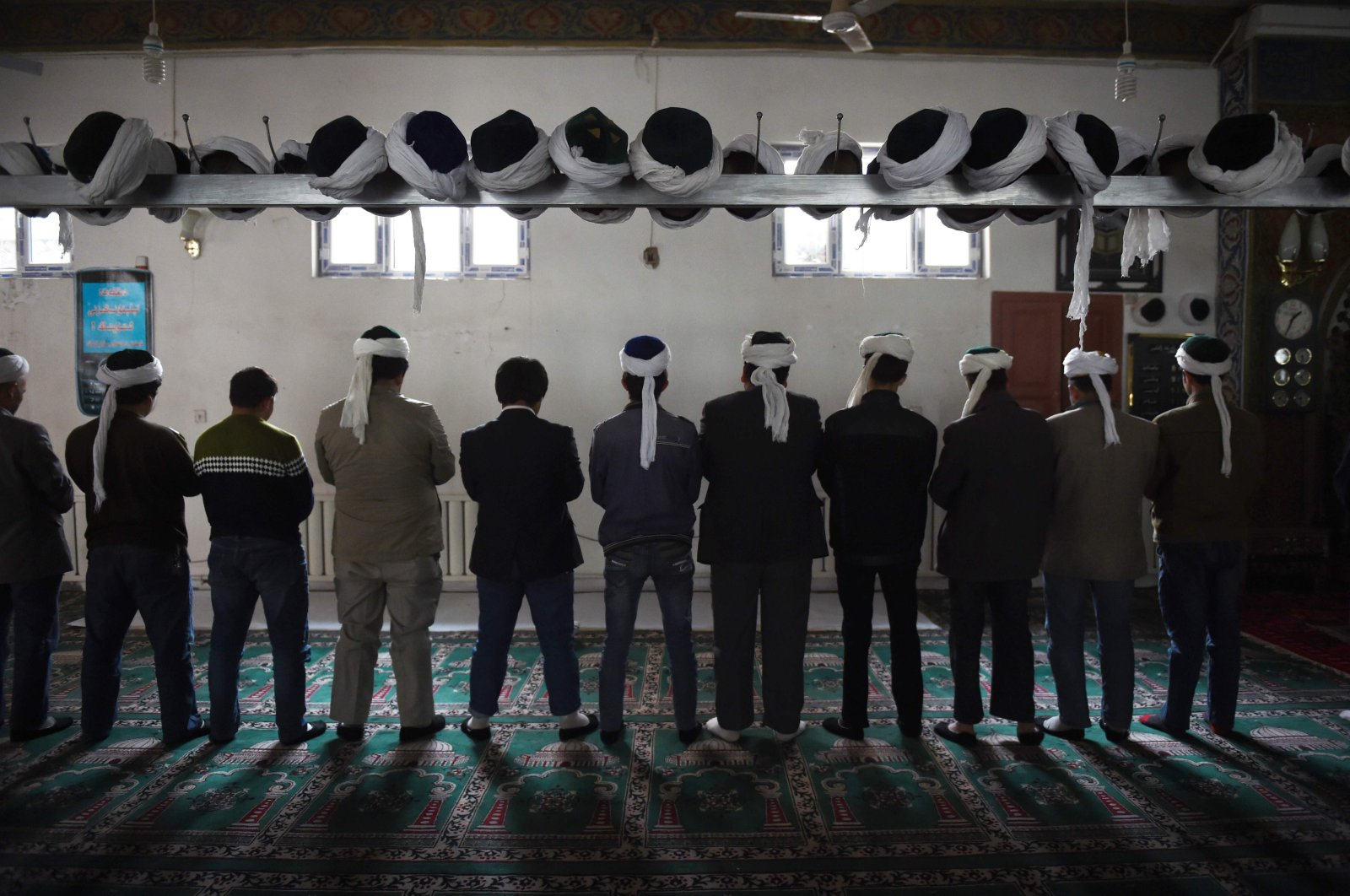 This file photo taken on April 16, 2015 shows Uighur men praying in a mosque in Hotan, in China's western Xinjiang region.(AFP Photo)