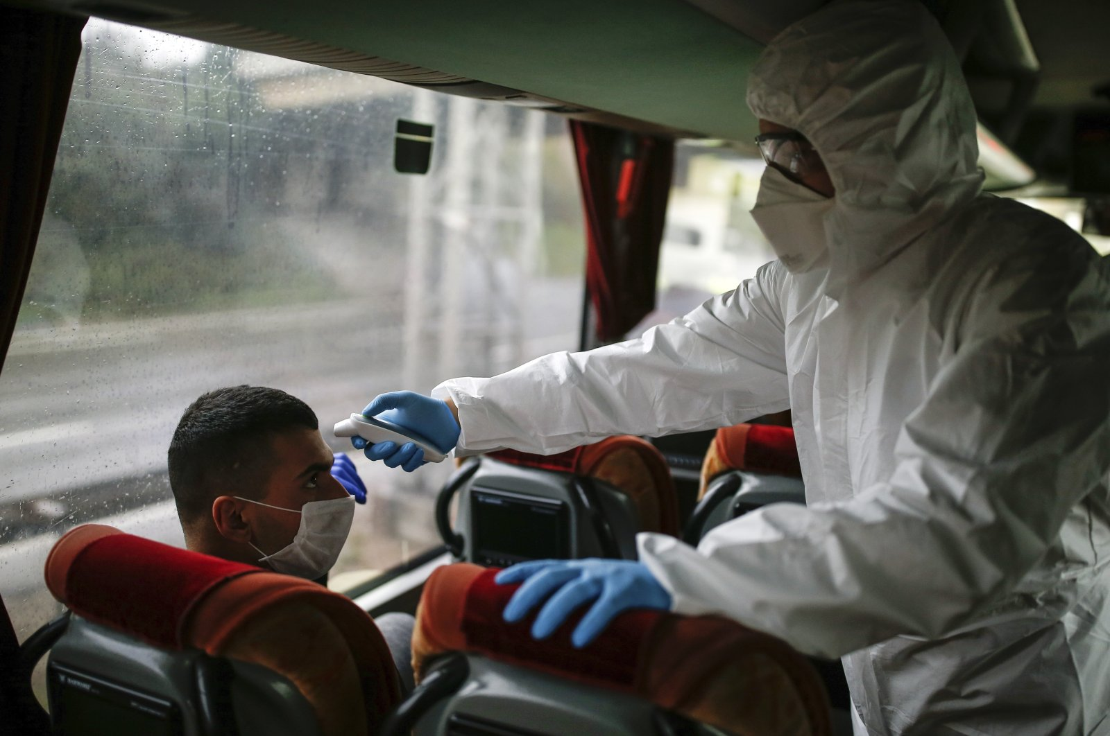 A health official measures the body temperature of a passenger on a bus at a checkpoint, on the Asian side of Istanbul, March 29, 2020. (AP Photo)
