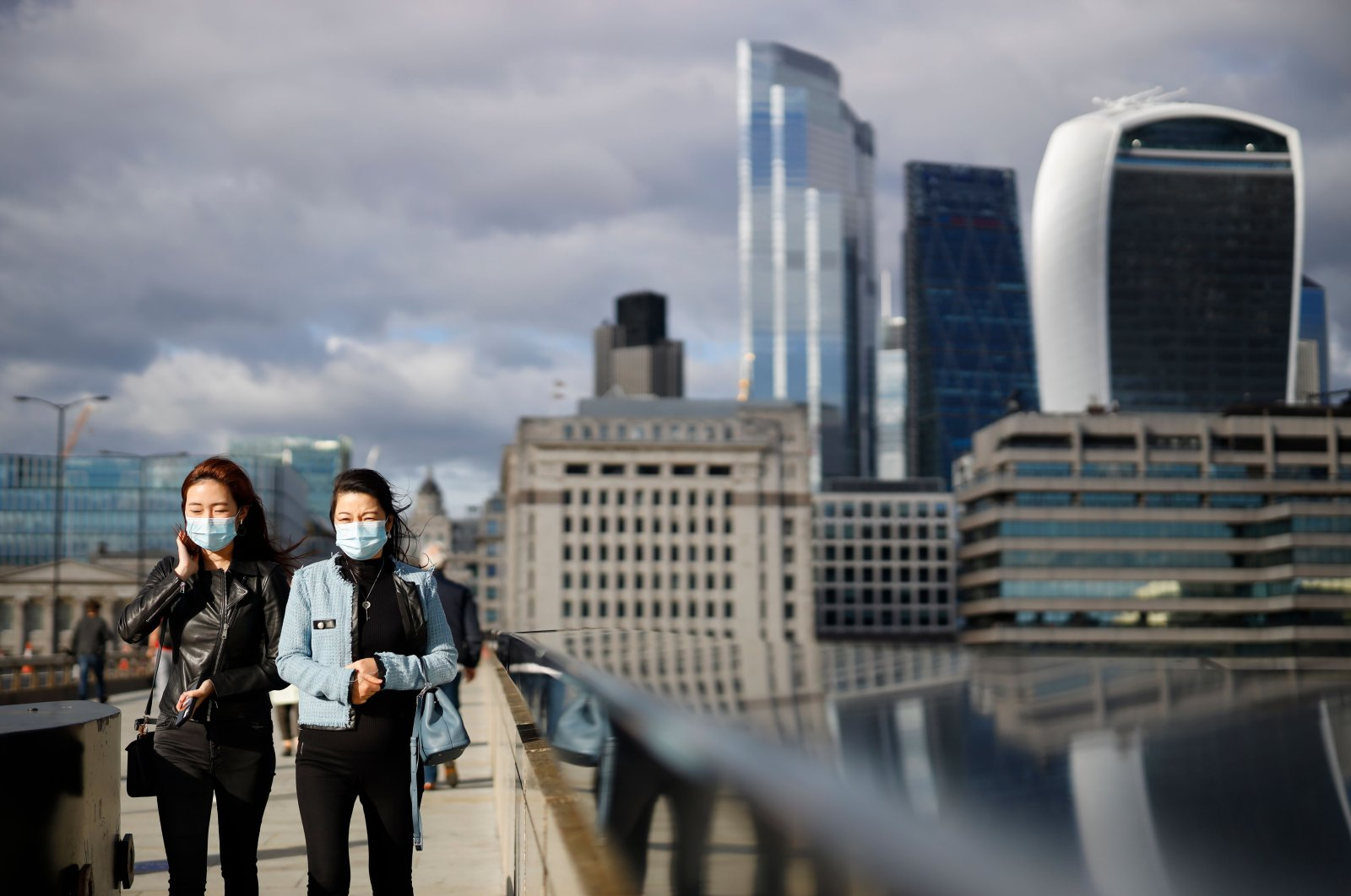 Pedestrians wear facemasks due to the novel coronavirus COVID-19 pandemic as they cross London Bridge in central London on Sept. 25, 2020. (AFP Photo)
