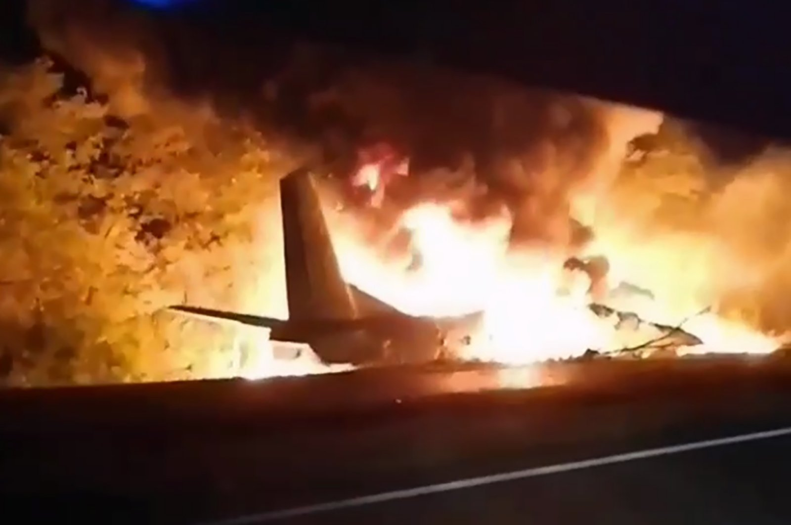 In this TV grab released by Ukraine's Emergency Situation Ministry, an AN-26 military plane bursts into flames after it crashed in the town of Chuguyiv close to Kharkiv, Ukraine, late Sept. 25, 2020. (Emergency Situation Ministry Photo via AP)