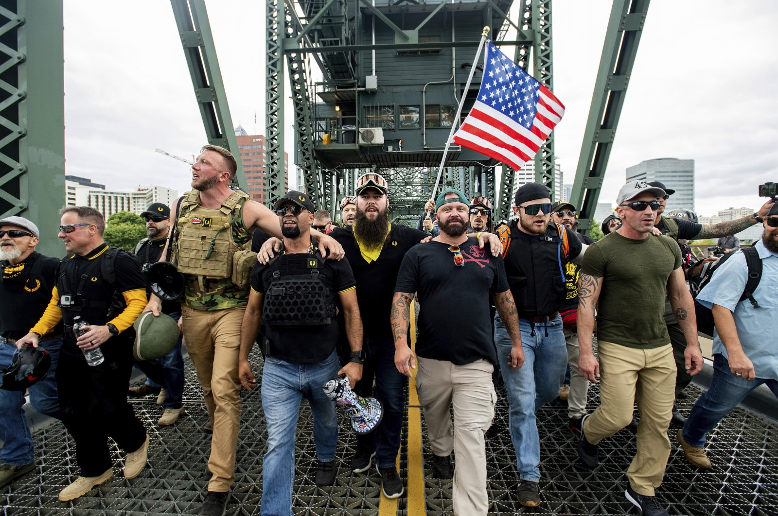 In this Aug. 17, 2019, file photo, members of the Proud Boys and other right-wing demonstrators march across the Hawthorne Bridge during a rally in Portland. At least several thousand people are expected in Portland on Sept. 26, 2020, for a rally in support of President Donald Trump and his re-election campaign as tensions boil over nationwide following the decision not to charge officers for killing Breonna Taylor. (AP Photo)