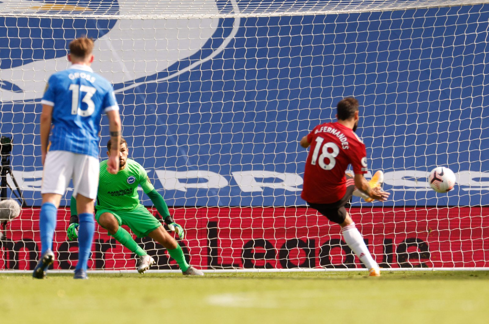 Manchester United's Portuguese midfielder Bruno Fernandes (R) takes a penalty and scores his team's third goal during the English Premier League football match between Brighton and Hove Albion and Manchester United at the American Express Community Stadium in Brighton, southern England on September 26, 2020. (AFP Photo)