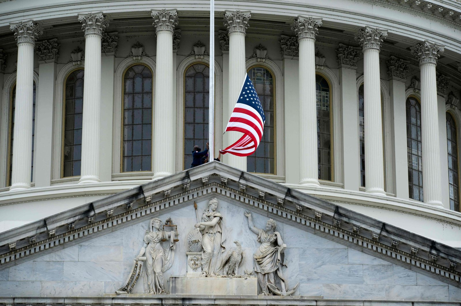 Workers fly the American flag at half staff over the US Capitol building in Washington, D.C., on Sept. 25, 2020. (AFP Photo)