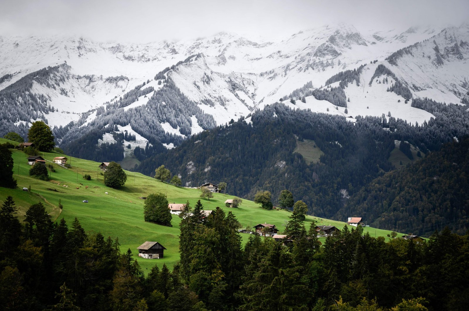 Chalets can be seen near fresh snow in Kiental, Bernese Oberland as cold winds and a sharp drop in temperatures have brought the first signs of winter to the Swiss Alps, Sept. 26, 2020.  (AFP Photo)