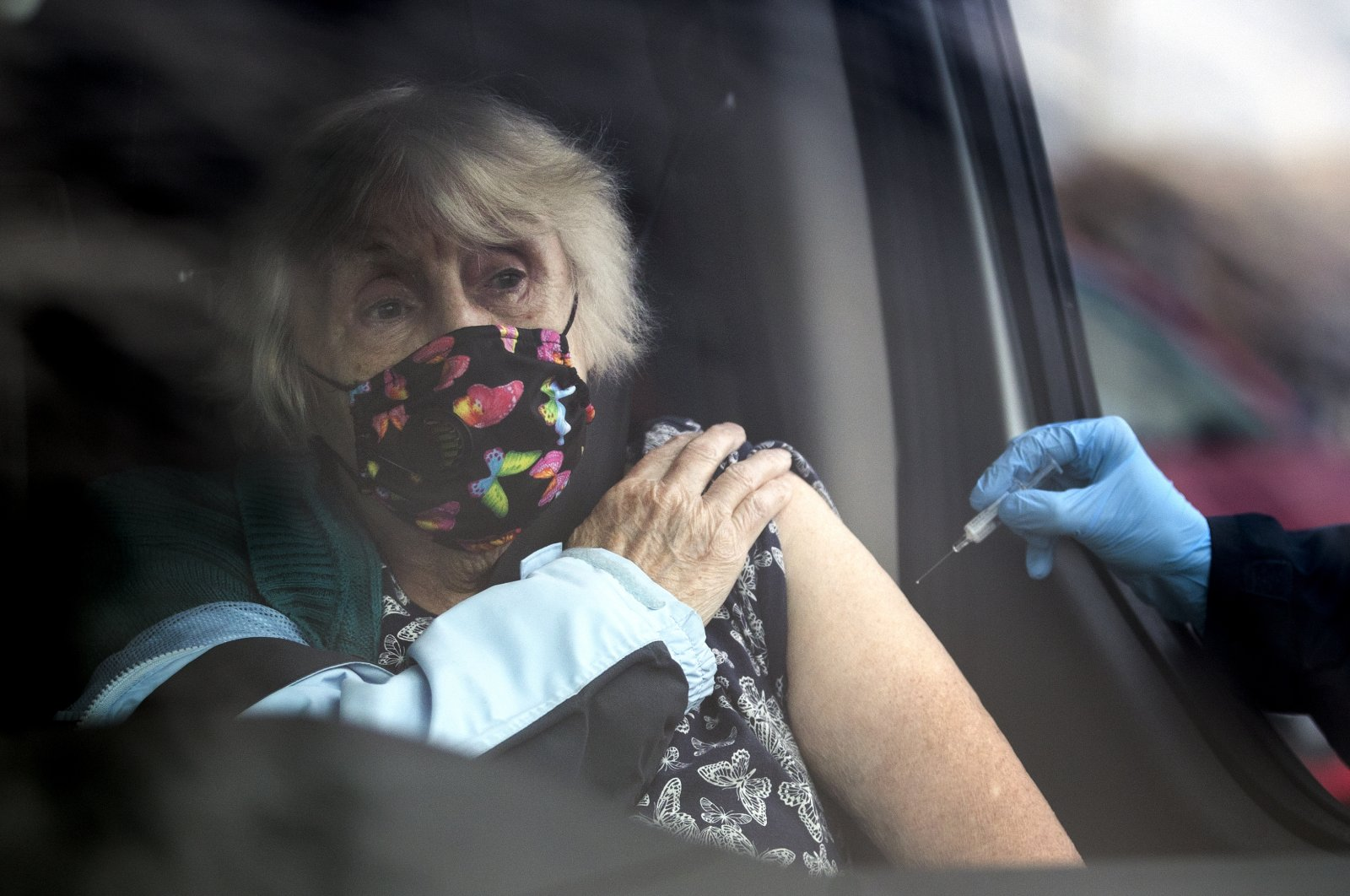 A member of the public receives a flu vaccine sat in their car at one of the new drive-thru flu clinics at Little France, Edinburgh. (PA via Reuters)