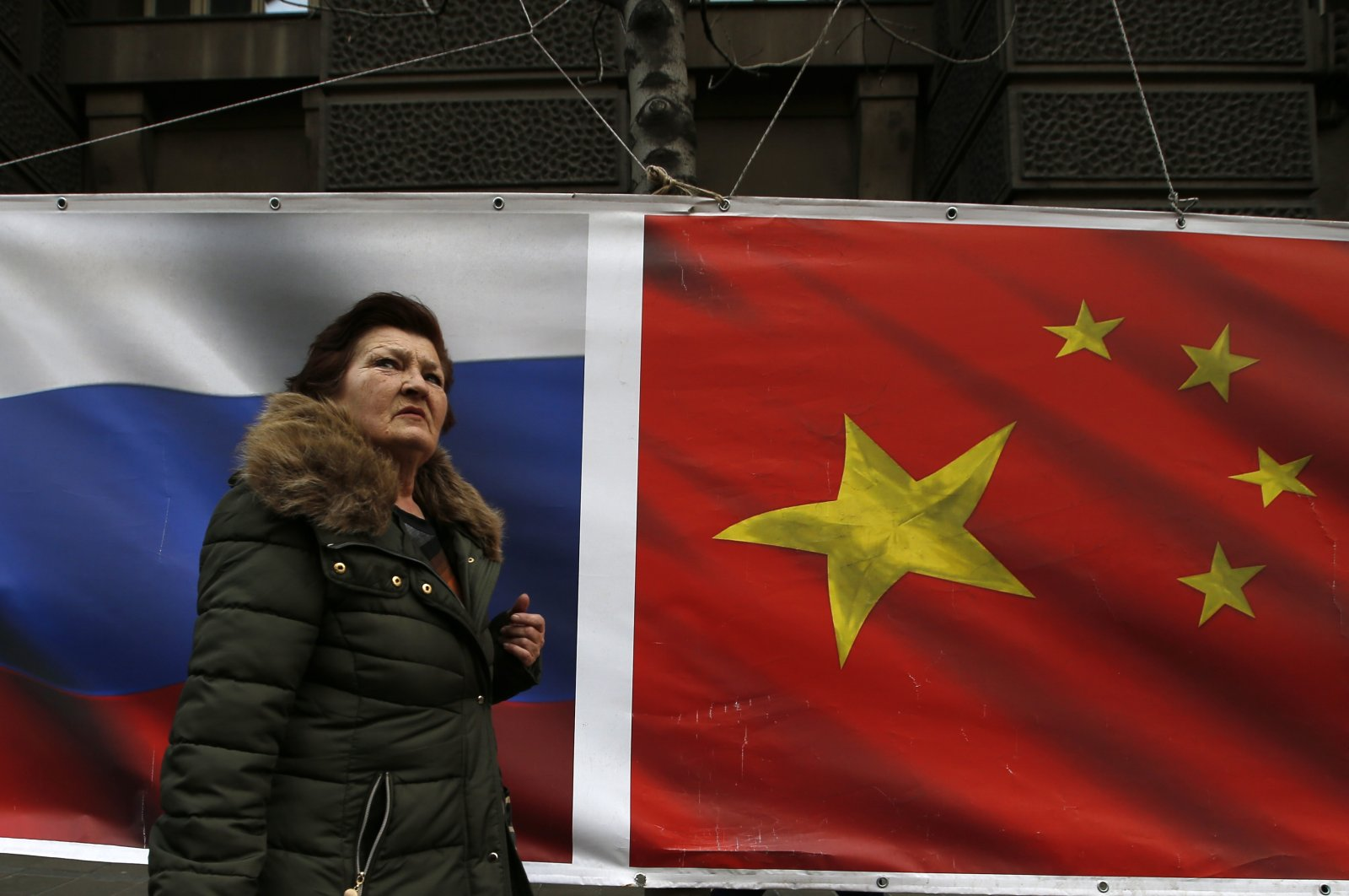 A woman walks by Russian and Chinese flags placed on a street in Belgrade, Serbia, March 1, 2019. (AP Photo)