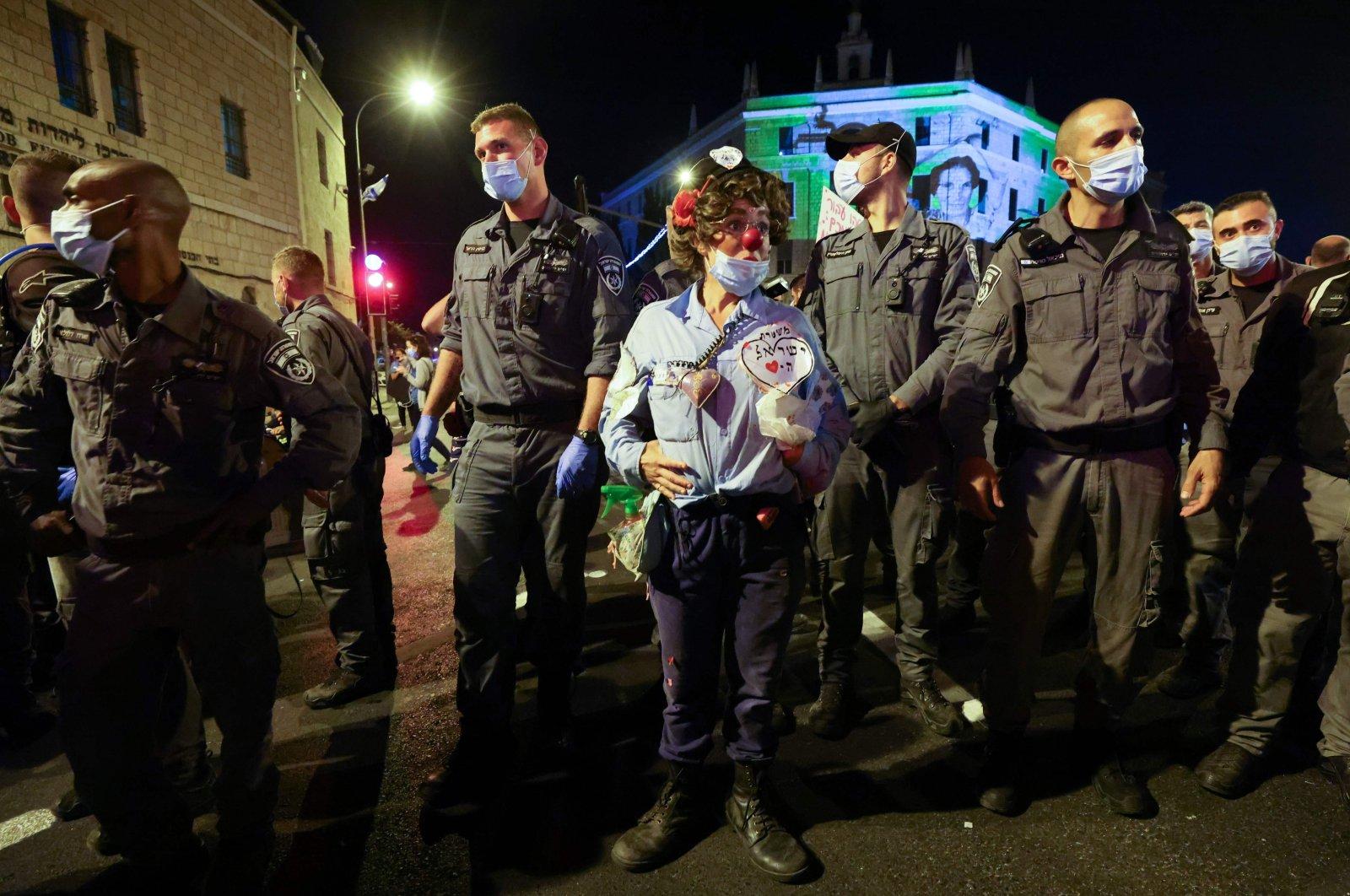 An Israeli protester stand amongst policemen during a demonstration in front of Prime Minister Benjamin Netanyahu's residence, Jerusalem, Sept. 26, 2020. (AFP Photo)