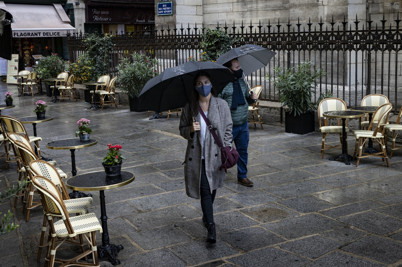 A couple of pedestrians wearing protective face masks walk past a deserted bistrot terrace, Paris, Sept. 25, 2020. (EPA Photo)
