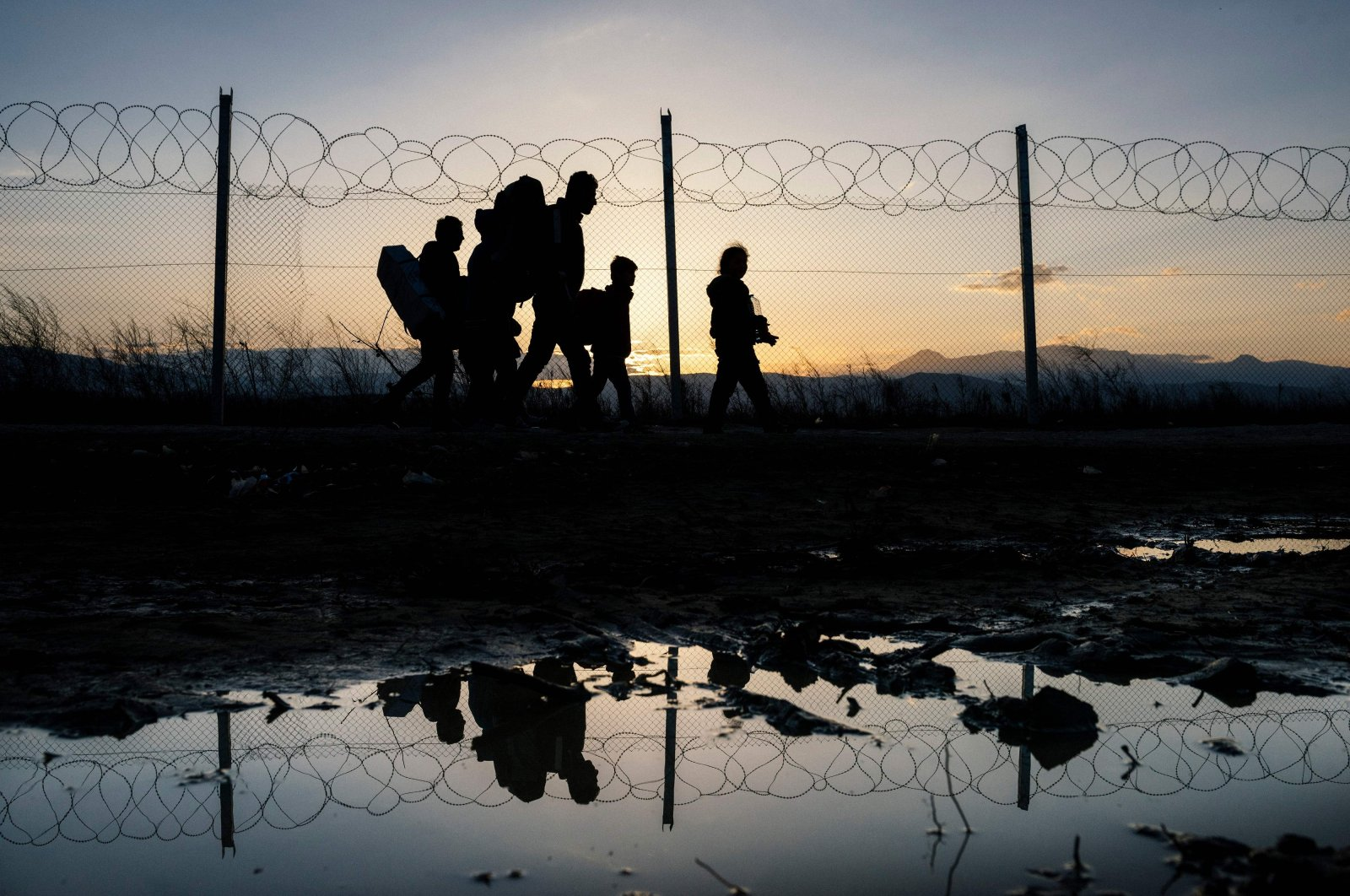 In this file photo, refugees walk to a registration camp after crossing the  Greek-Macedonian border, near the town of Gevgelija, after Macedonia allowed around 250 migrants to cross its border with Greece, as 10,000 more were left waiting in miserable conditions, March 2, 2016. (AFP Photo)