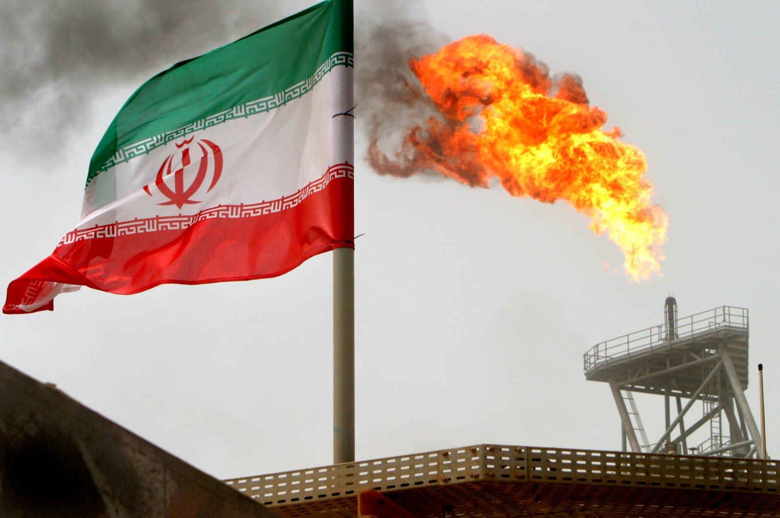 A gas flare on an oil production platform in the Soroush oil fields is seen alongside an Iranian flag in the Persian Gulf, Iran, July 25, 2015. (Reuters Photo)