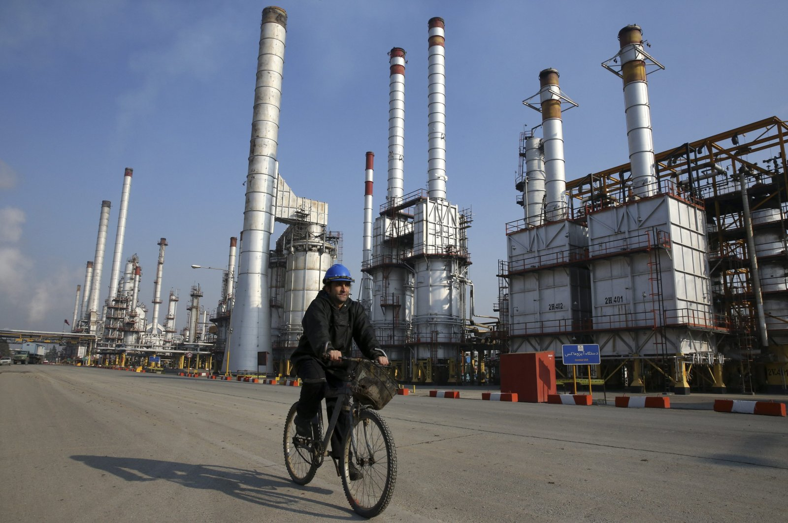 An Iranian oil worker rides his bicycle at Tehran's oil refinery south of the capital Tehran, Iran, Dec. 22, 2014. (AP Photo)
