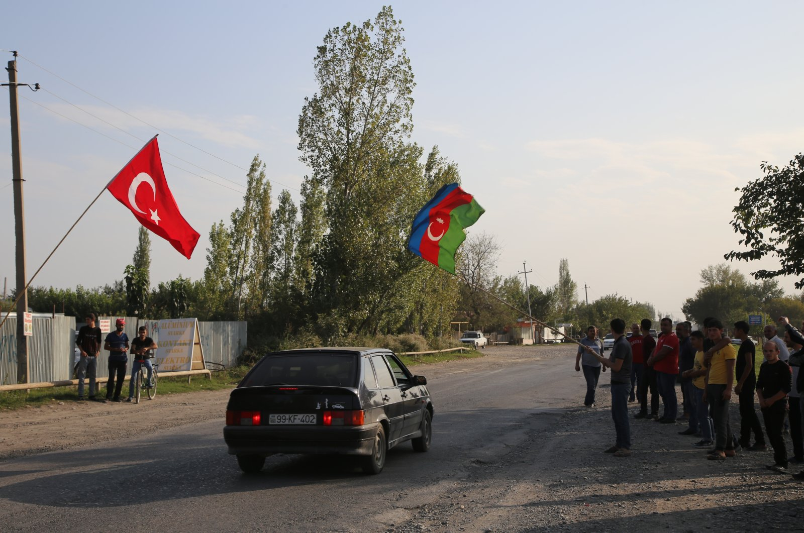 Villagers wave Turkish and Azerbaijani flags at a village in western Azerbaijan as clashes resume in the Armenian-occupied Nagorno-Karabakh region, on Sep. 27, 2020. (AA Photo)