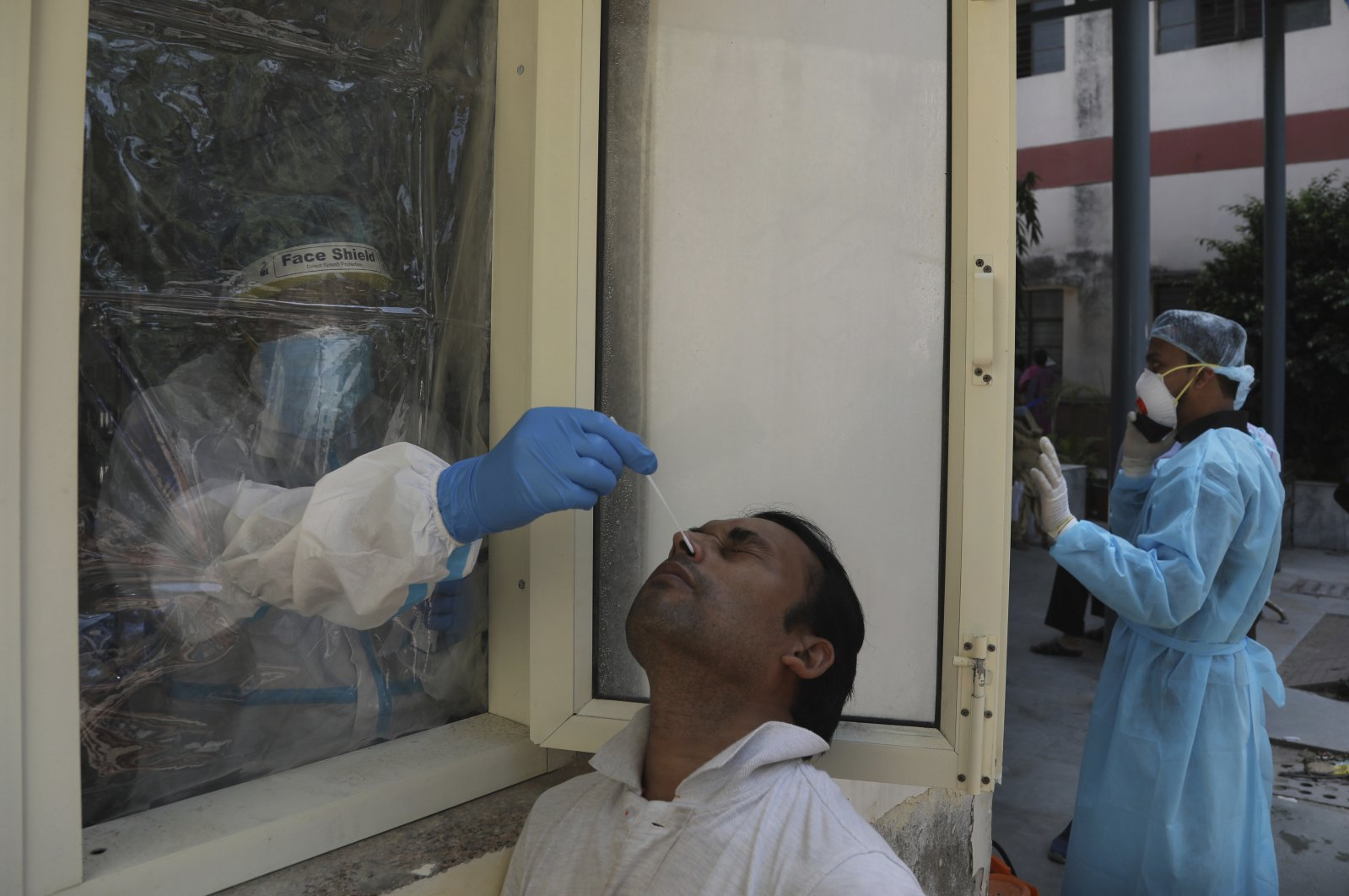 A health worker conducts COVID-19 test at a government hospital, New Delhi, Sept. 28, 2020. (AP Photo)