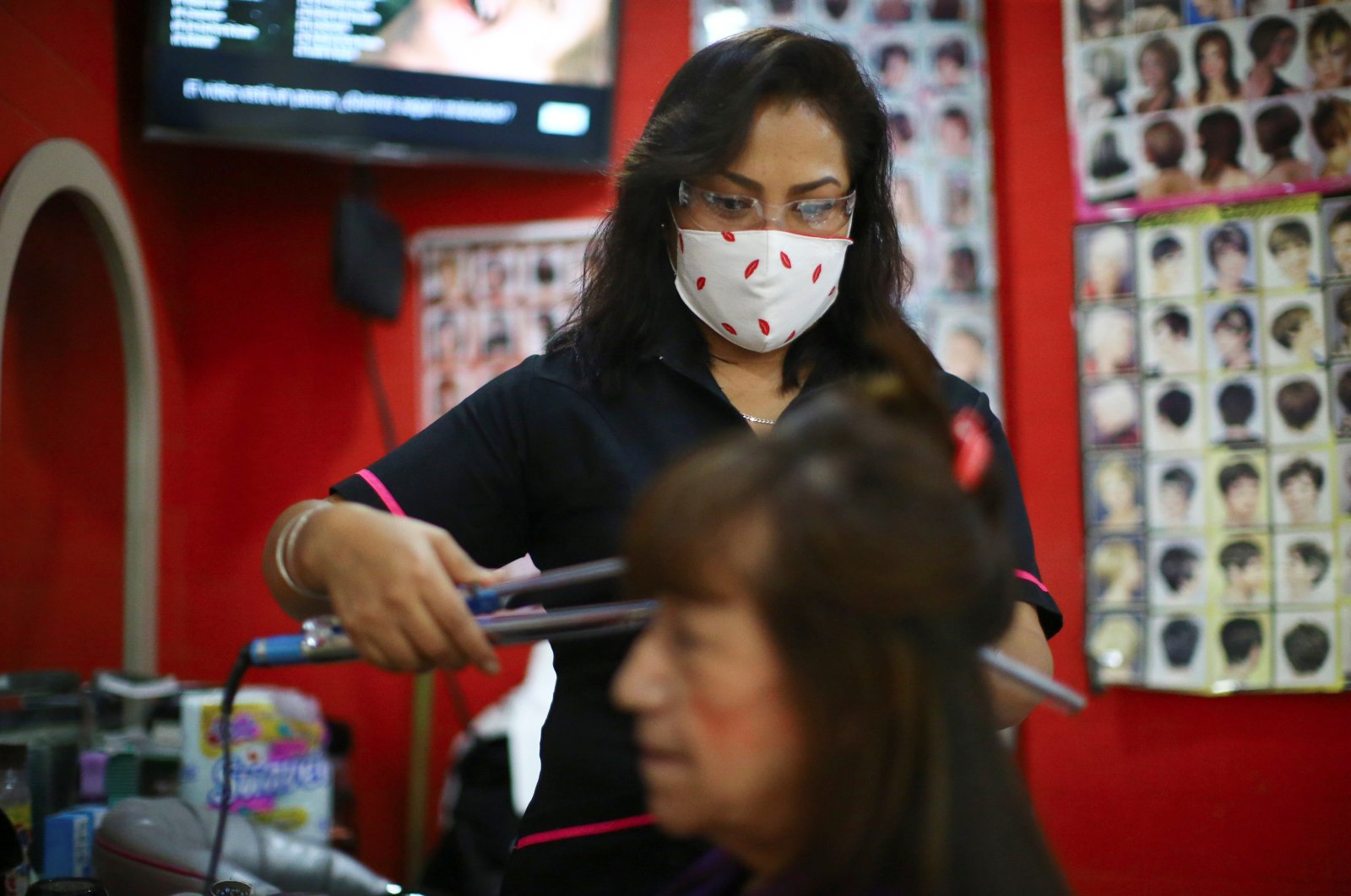 A stylist wearing a face mask combs a woman's hair at a beauty salon in Mexico City, Mexico, Sept. 22, 2020. (Reuters Photo)