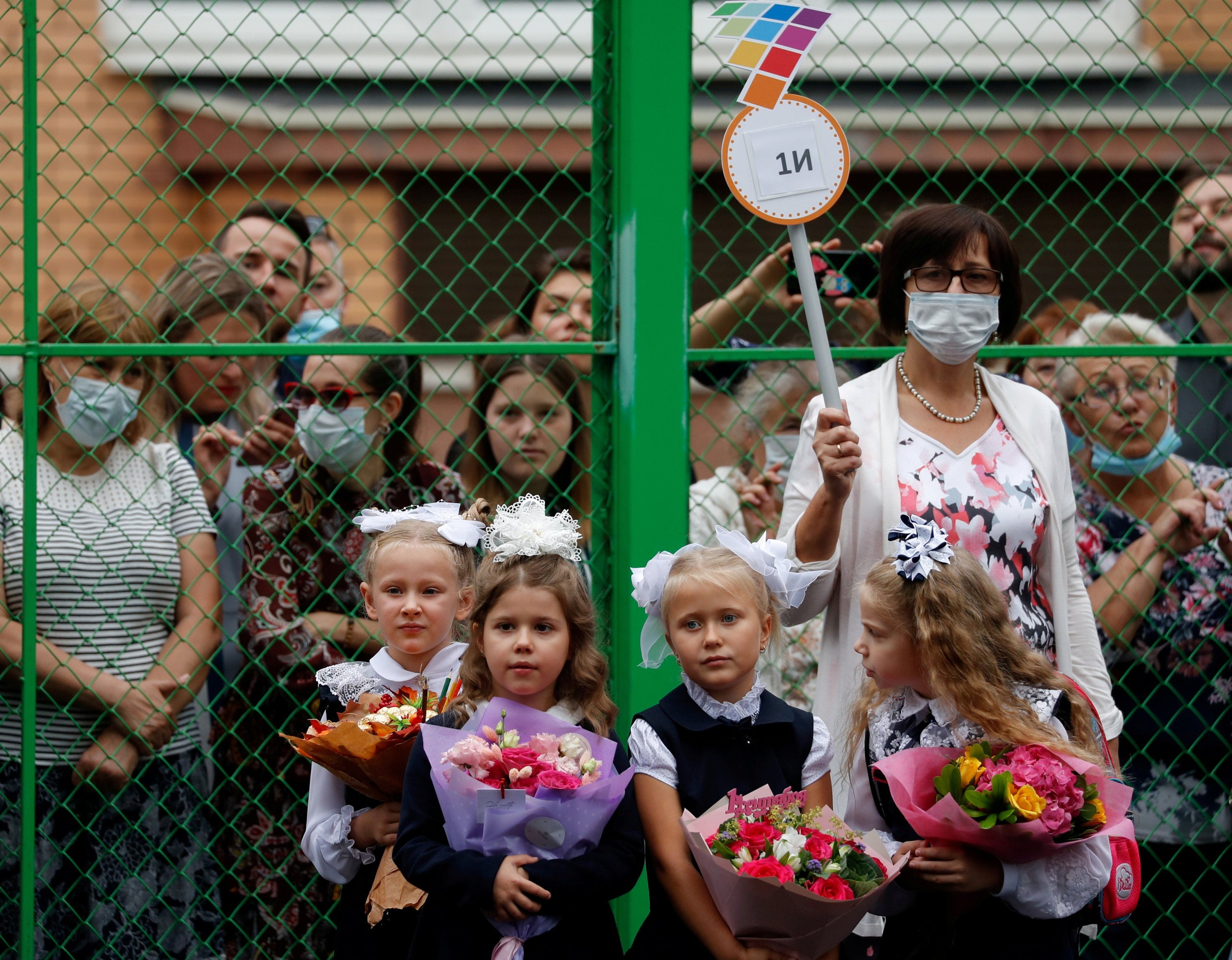 A teacher wears a face mask as she stands next to first graders during a ceremony marking the start of the new school year in Moscow, Russia September 1, 2020. (REUTERS Photo)