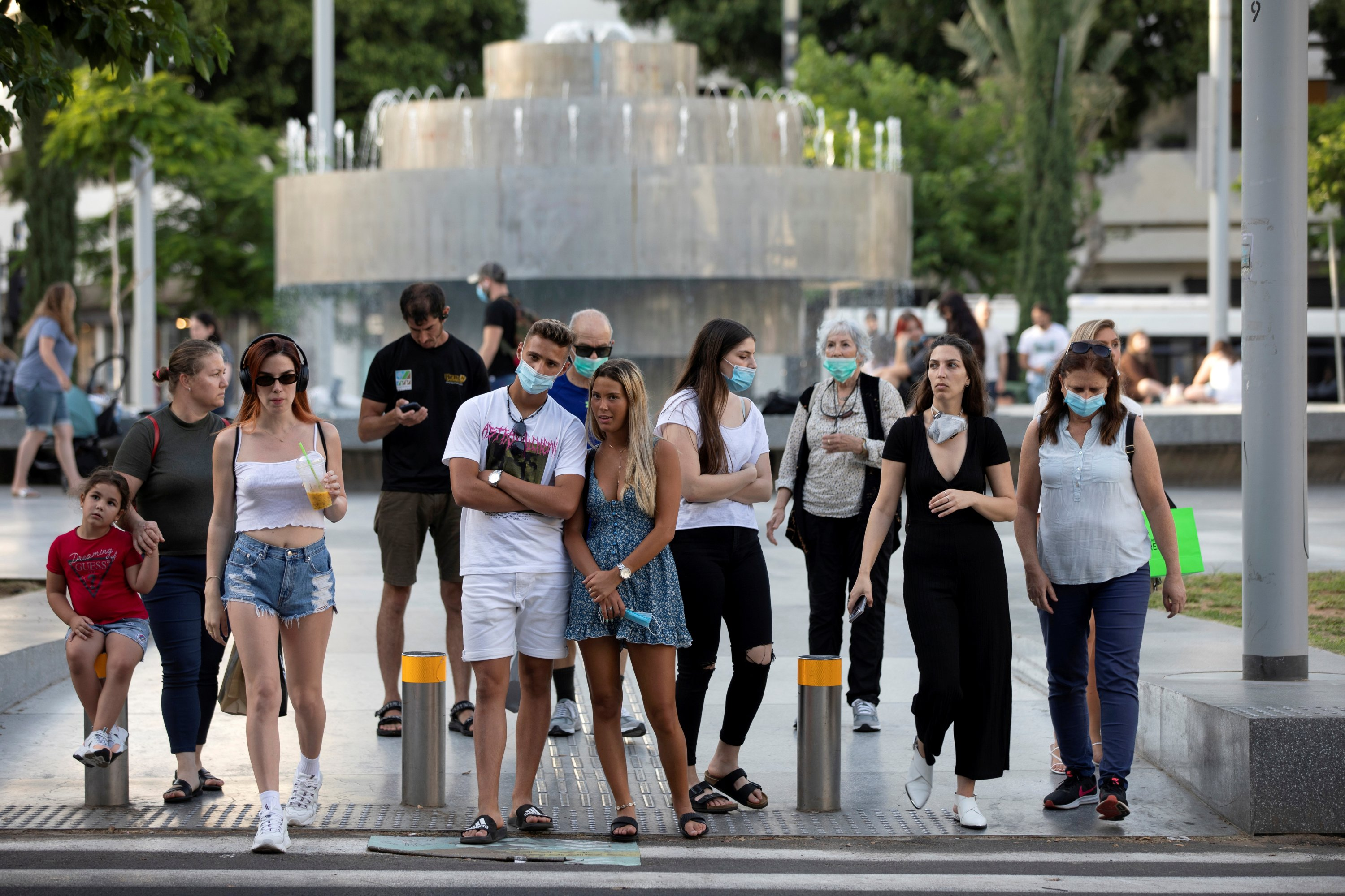 Pedestrians, some wearing masks, prepare to cross the street as some businesses reopened at the end of last month under a host of new rules, in Tel Aviv, Israel June 4, 2020. Picture taken June 4, 2020. (REUTERS Photo)