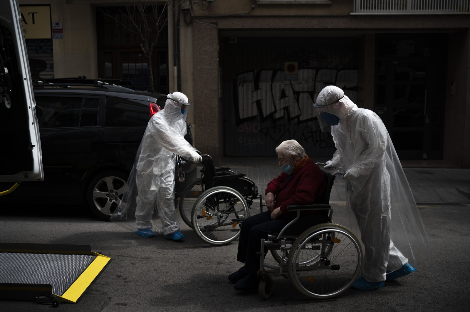 A volunteer of the Spanish nongovernmental organization Open Arms pushes an elderly resident of a nursing home who has coronavirus symptoms in a wheelchair to a hospital in Barcelona, Spain, April 11, 2020. (AP Photo)