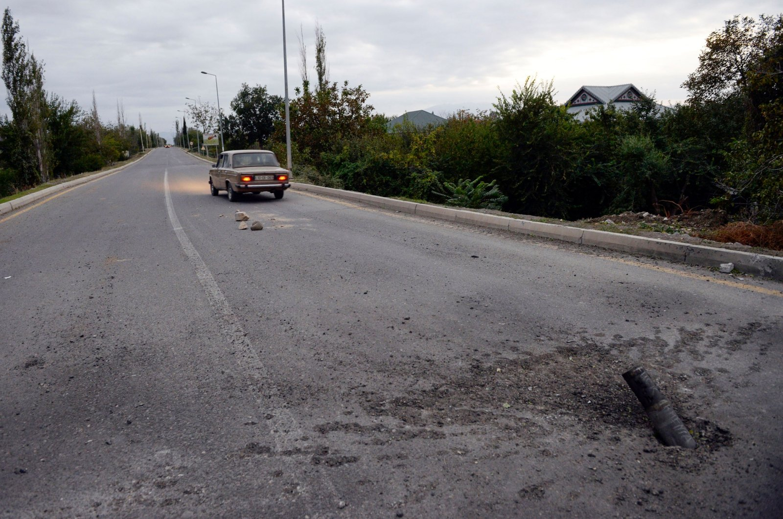 An unexploded artillery shell fired by Armenian separatists on a road on the outskirts of Tartar, Azerbaijan, Sept. 28, 2020. (AFP Photo)