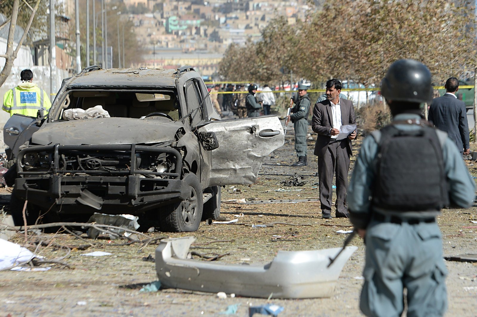 Afghan investigators inspect wreckage at the site where a suicide bomber targeted a vehicle convoy of Afghan lawmakers in Kabul on Nov. 16, 2014. (AFP Photo)