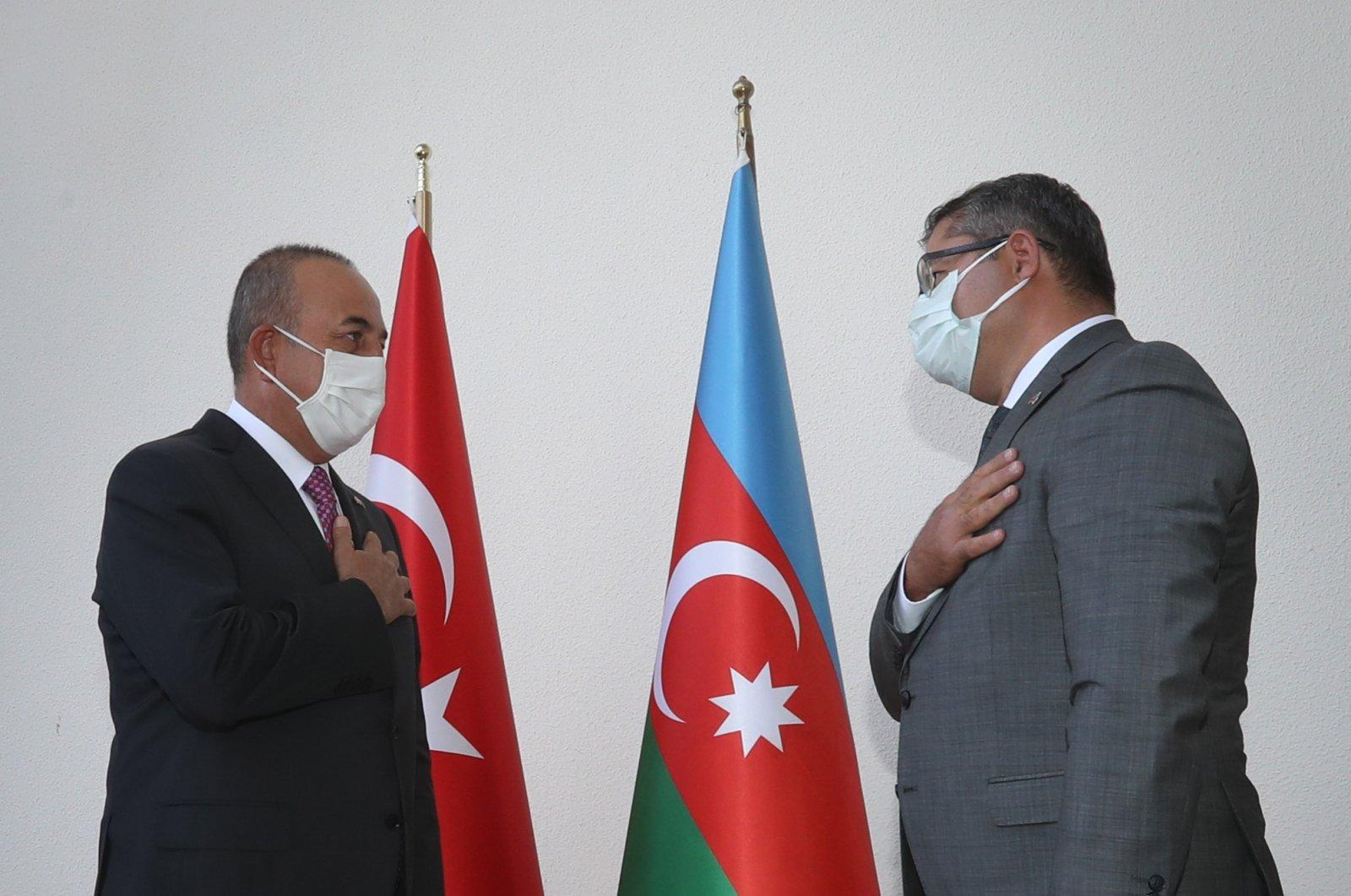 Foreign Minister Mevlüt Çavuşoğlu (L) and Azerbaijani Ambassador to Ankara Khazar Ibrahim gesture during the former's visit to the embassy in Ankara, Sept. 29, 2020 (AA Photo)