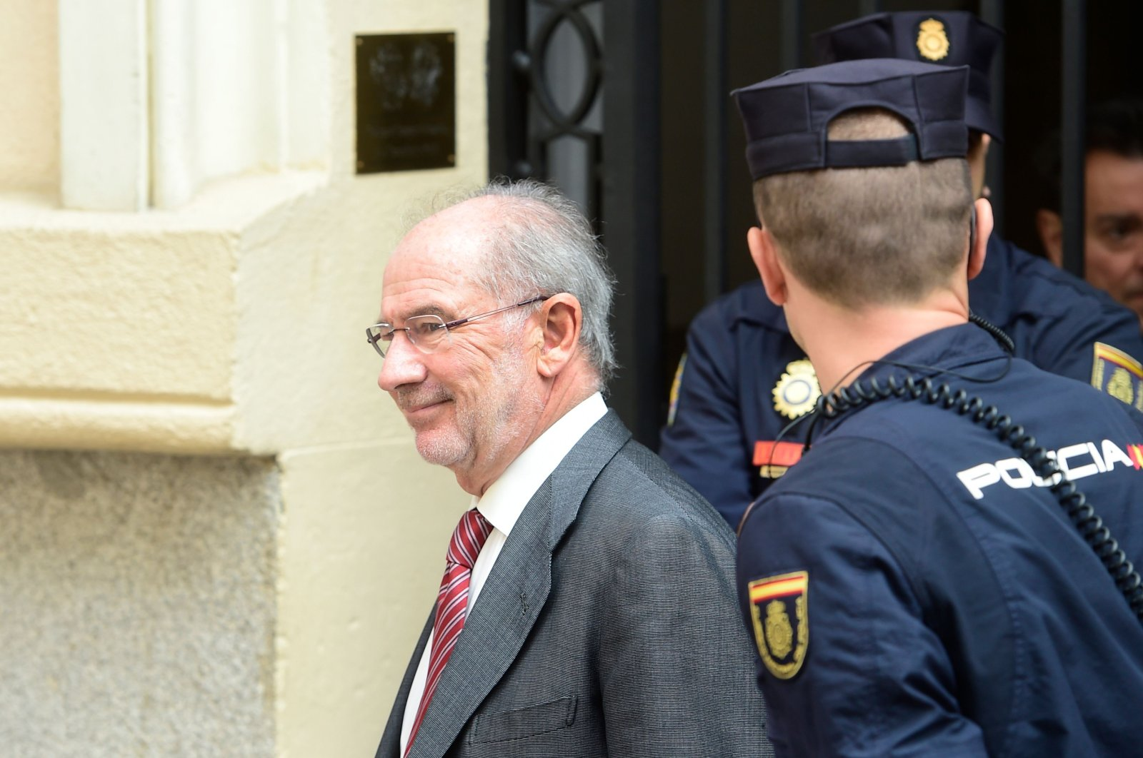 Former IMF head and former Spanish Economy minister Rodrigo Rato (L) smiles as he leaves his office, April 17, 2015. (AFP Photo)