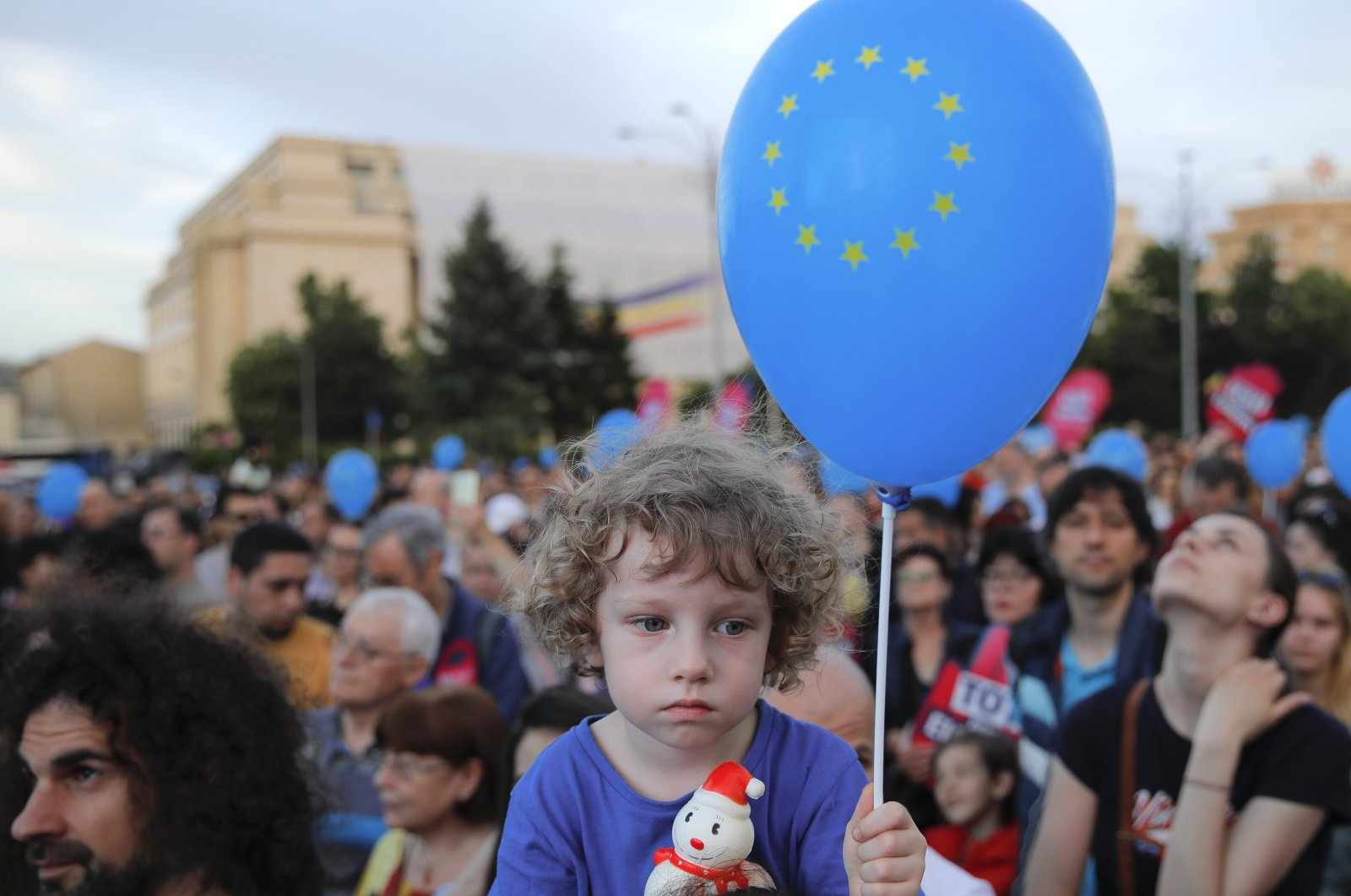 """A child holds a balloon depicting the European Union Flag during a pro-Europe event dubbed """"All for Europe"""" outside the government headquarters in Bucharest, Romania, May 19, 2019. (AP Photo)"""