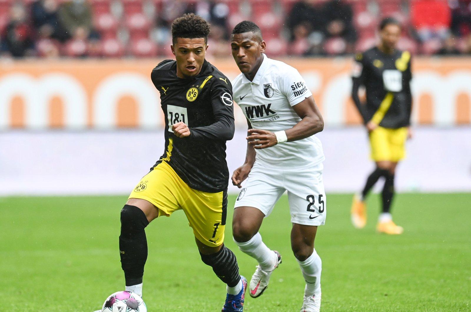 Borussia Dortmund's Jadon Sancho in action with FC Augsburg's Carlos Gruezo, Augsburg, Germany, Sept. 26, 2020. (Reuters Photo)