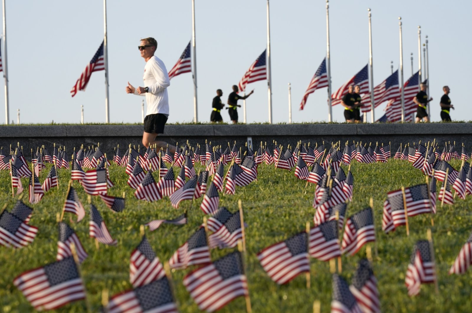 Morning joggers look over small flags that activists from the COVID-19 Memorial Project placed on the grounds of the National Mall to mark the 200,000 lives lost in the U.S. to COVID-19, in Washington, D.C., Sept. 22, 2020. (AP Photo)