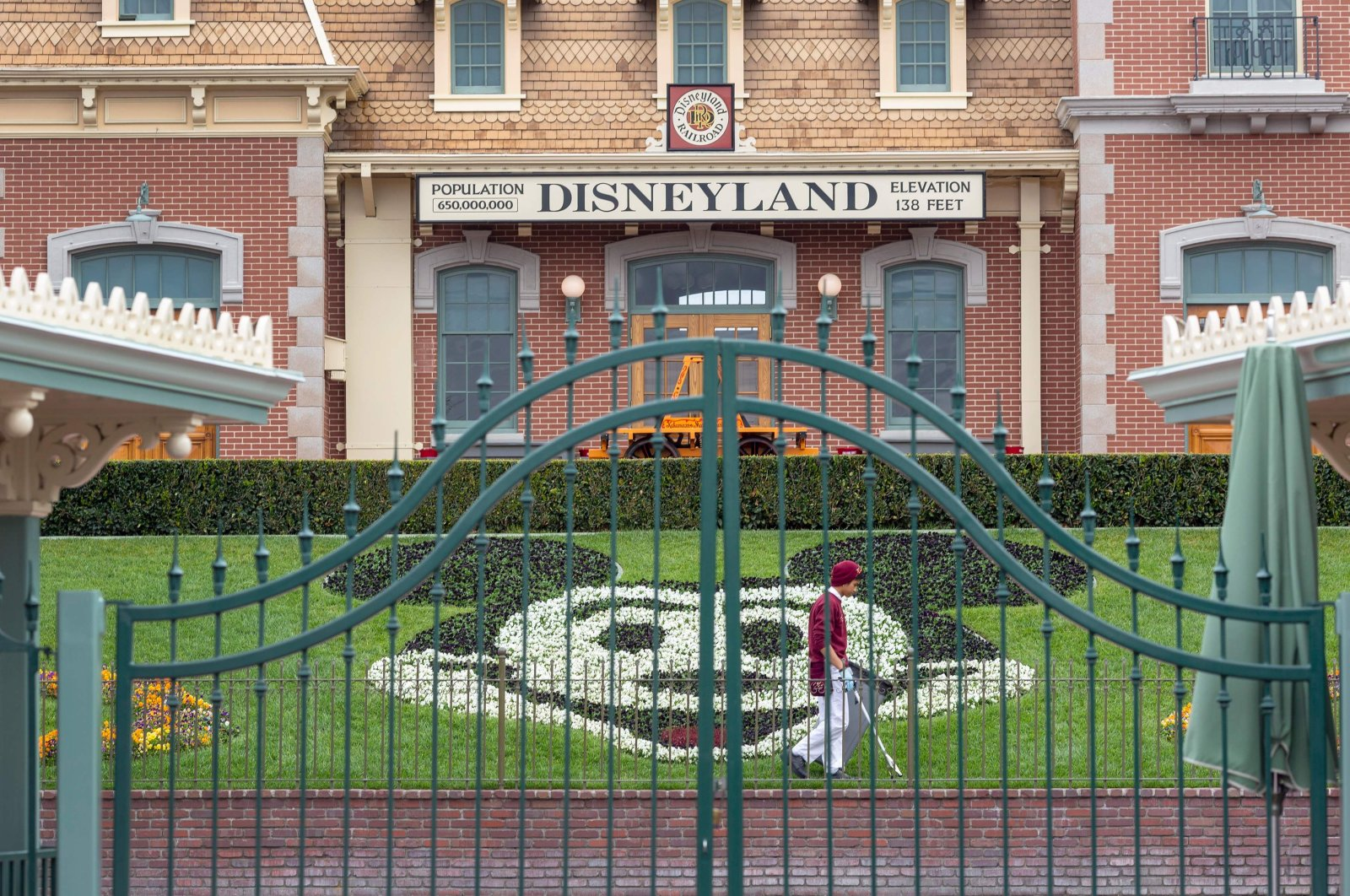 An employee cleans the grounds behind the closed gates of Disneyland Park on the first day of the closure of Disneyland and Disney California Adventure theme parks as fear of the spread of coronavirus continues, in Anaheim, California, March 14, 2020. (AFP Photo)