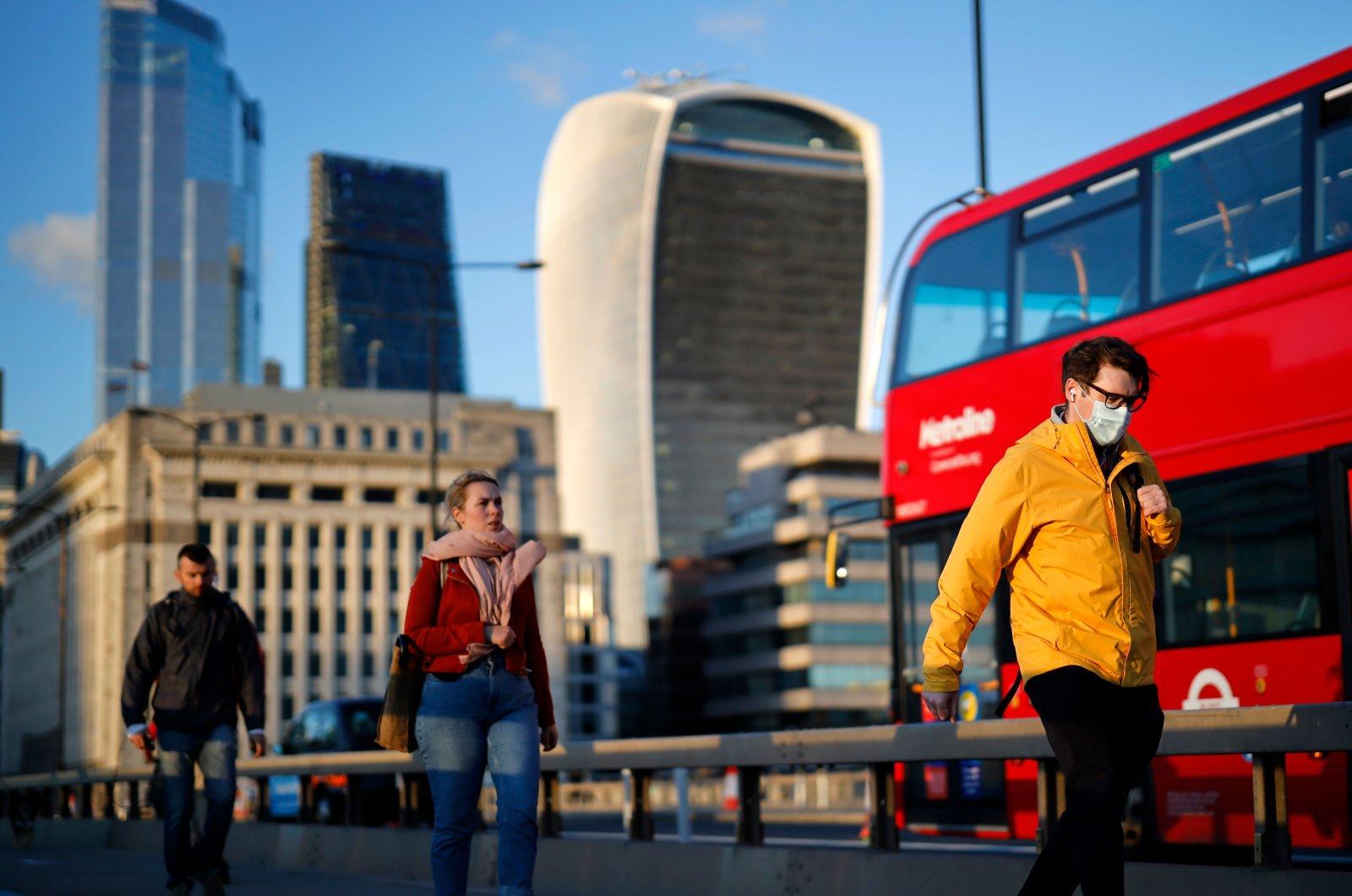 People cross London Bridge in the evening sunshine, in London, Sept. 25, 2020. (AFP Photo)