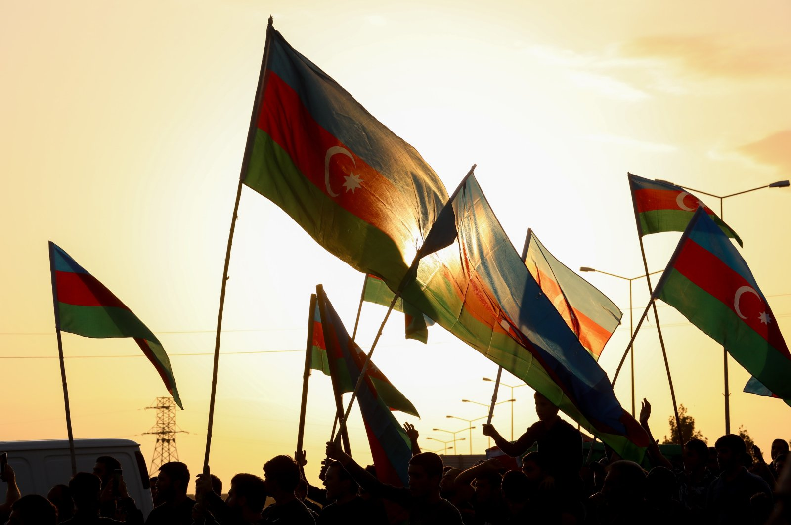 People wave flags at the funeral of a member of Azerbaijani military, who was killed by Armenian shelling in the Tartar border district of Azerbaijan, Sept. 29, 2020. (Photo by Getty Images)