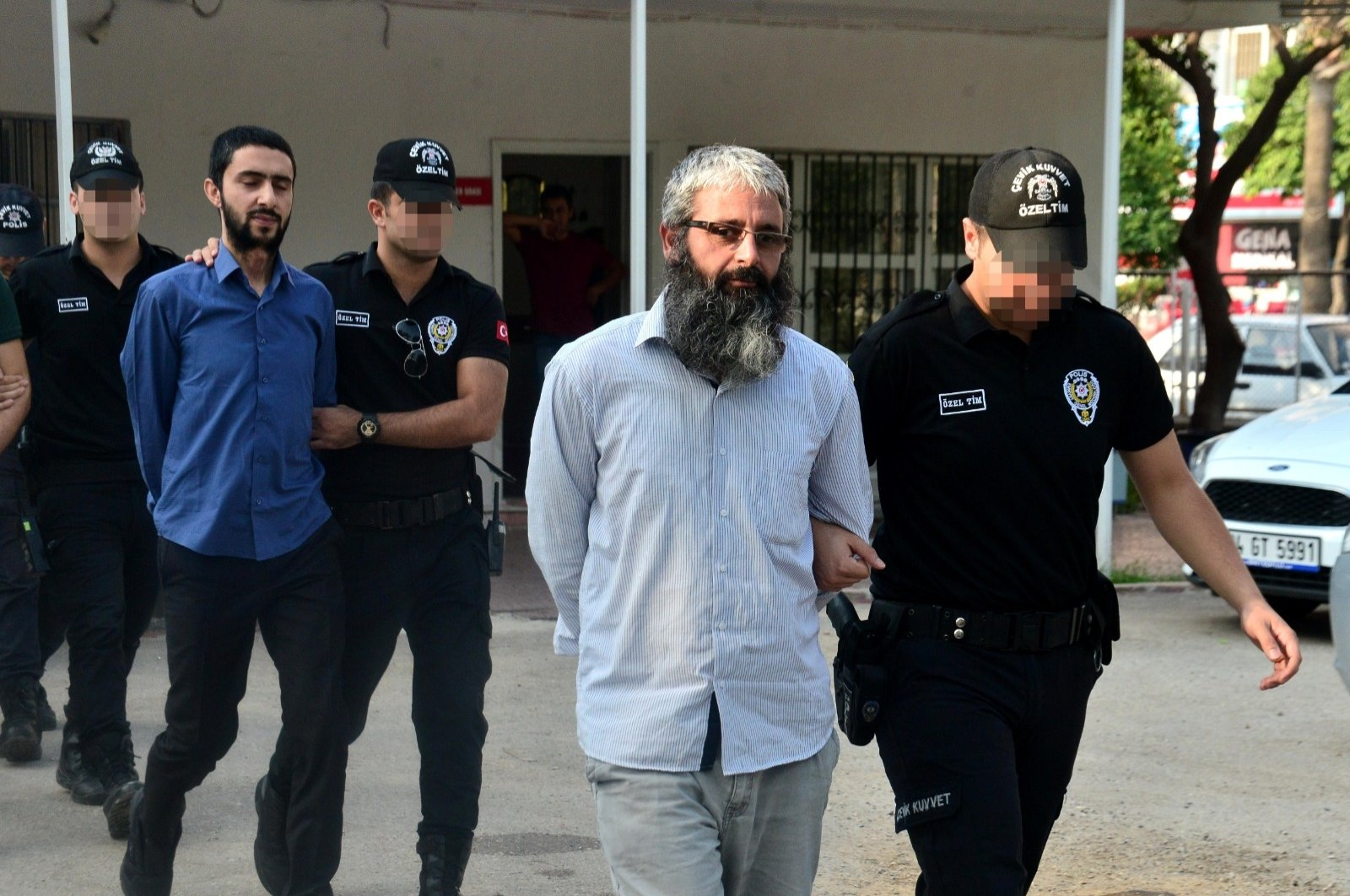 """The so-called """"Turkey emir"""" of Daesh terrorist group, Mahmut Özden and another suspect behind him are transferred by Turkish security forces to the courtroom in Adana, southern Turkey, Sept. 1, 2020 (DHA Photo)"""