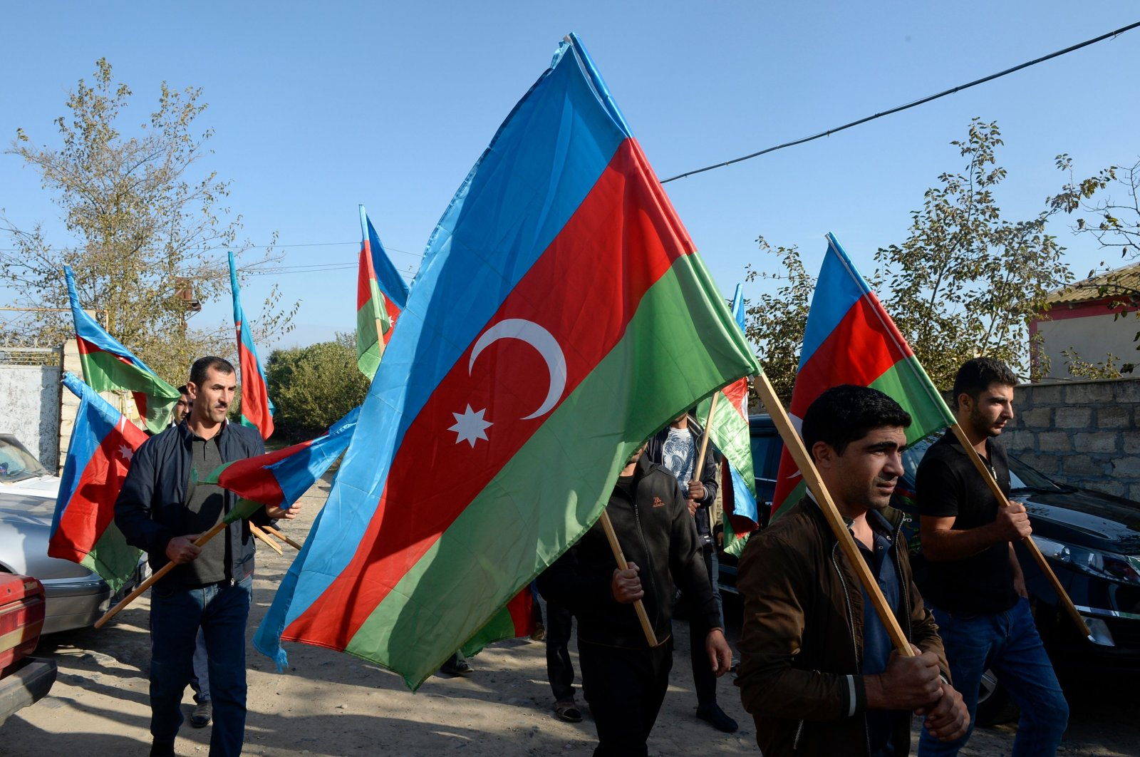 Men walk with Azerbaijani flags during a funeral procession of an Azeri serviceman who was to have been killed in fighting with Armenian separatists, Azerbaijan's Beylagan district, Sept. 30, 2020. (AFP)