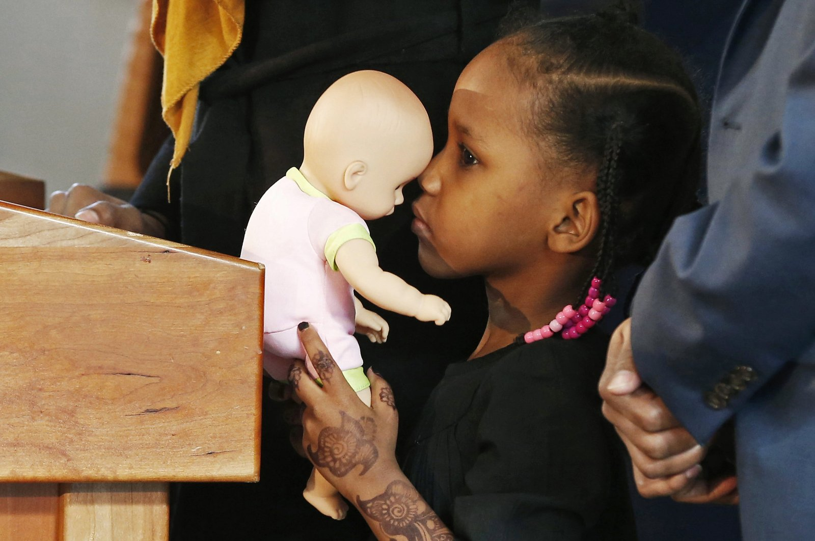 Four-year-old Somali refugee Mushkaad Abdi holds her doll as her mother, Samira Dahir, talks during a Minneapolis news conference one day after she was reunited with her family, Feb. 3, 2017. (AP Photo)
