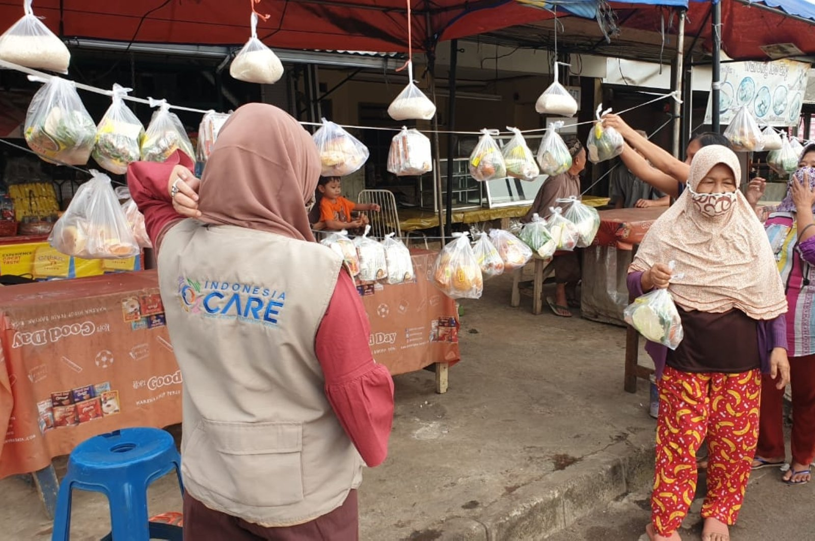 An Indonesia Care official and needy people take packages of groceries in Tangerang, southern Indonesia, Sept. 29, 2020. (AA Photo)