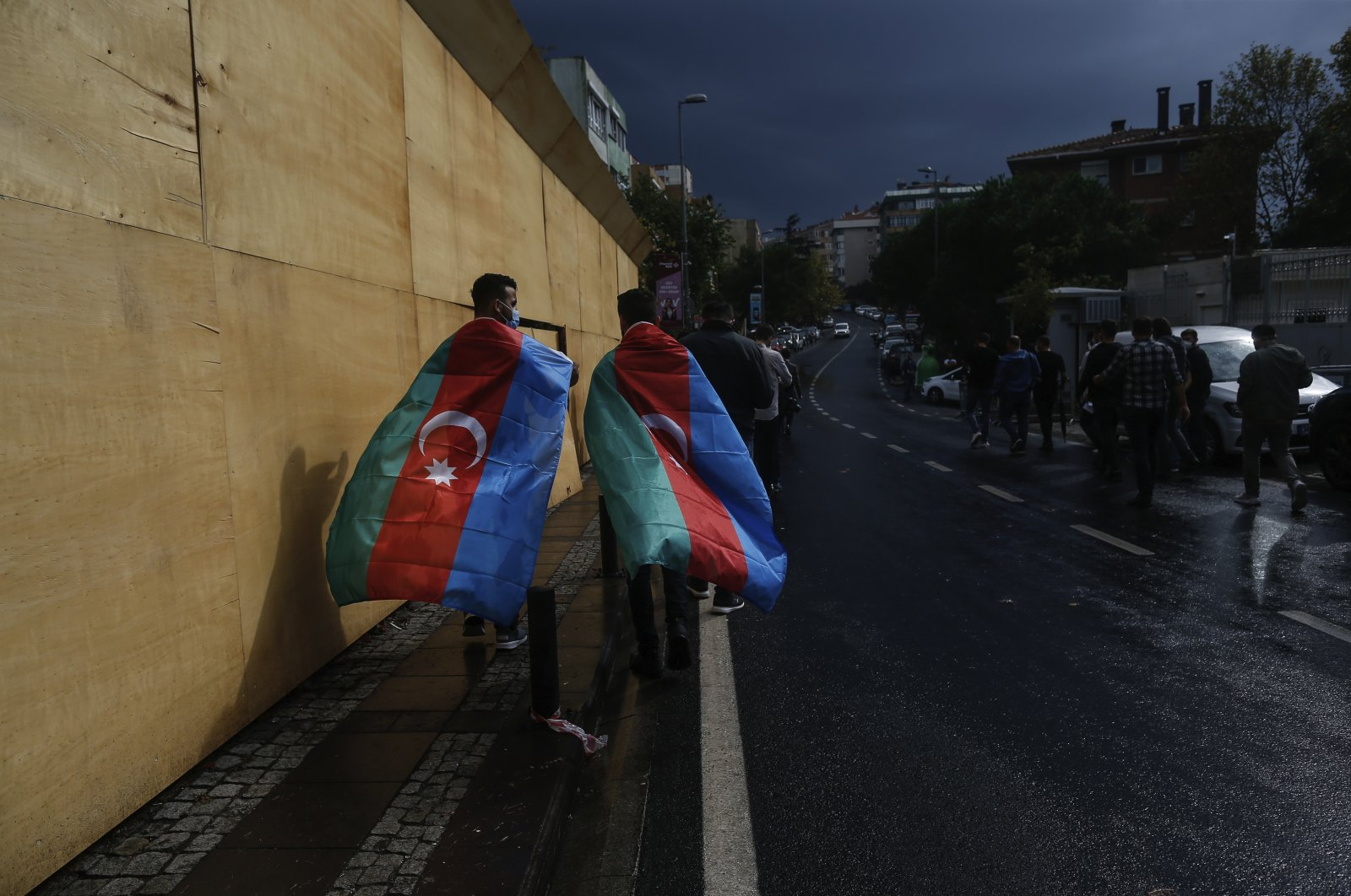 Two Turkish men, draped in Azerbaijani flags, walk away following a protest supporting Azerbaijan against Armenia's aggression, in front of the Azerbaijani Consulate in Istanbul, Turkey, Sept. 29, 2020. (AP Photo)