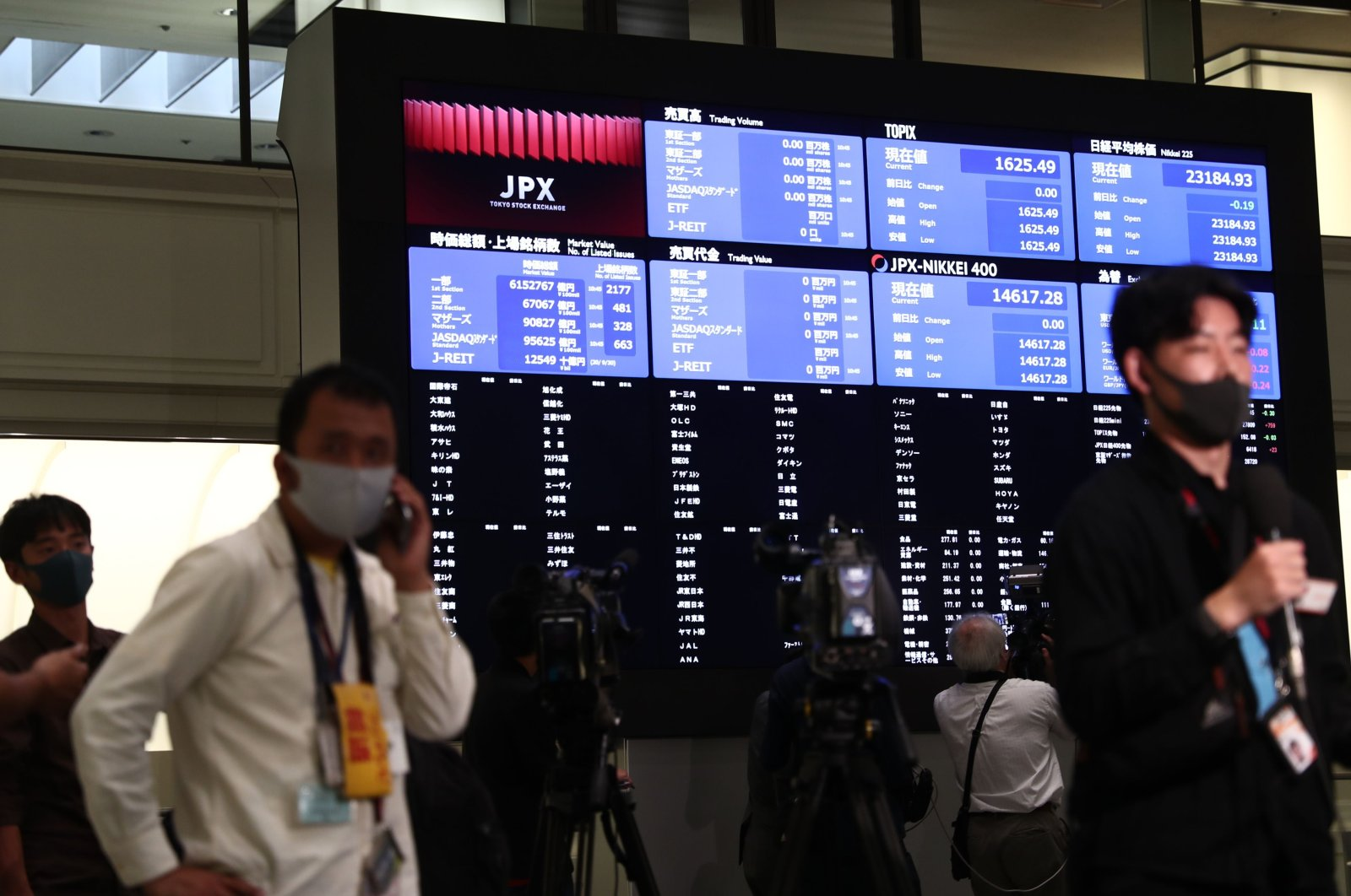 Journalists gather next to an information board inside the Tokyo Stock Exchange where trading was halted due to a glitch on the market in Tokyo, Oct. 1, 2020. (AFP Photo)