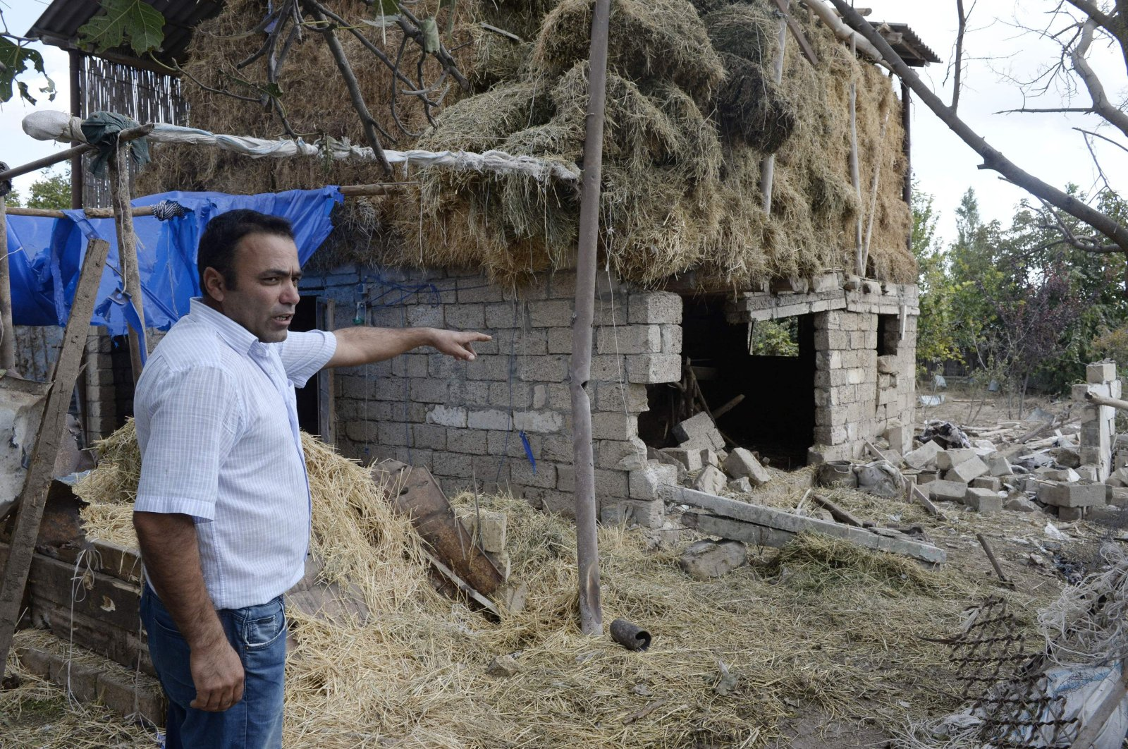 A man points to a house reportedly damaged by the recent fighting between Armenia and Azerbaijan over the Armenian occupied Nagorno-Karabakh region, in the settlement of Zorocuq in Azerbaijan's Fuzuli district, Sept. 30, 2020. (AFP Photo)
