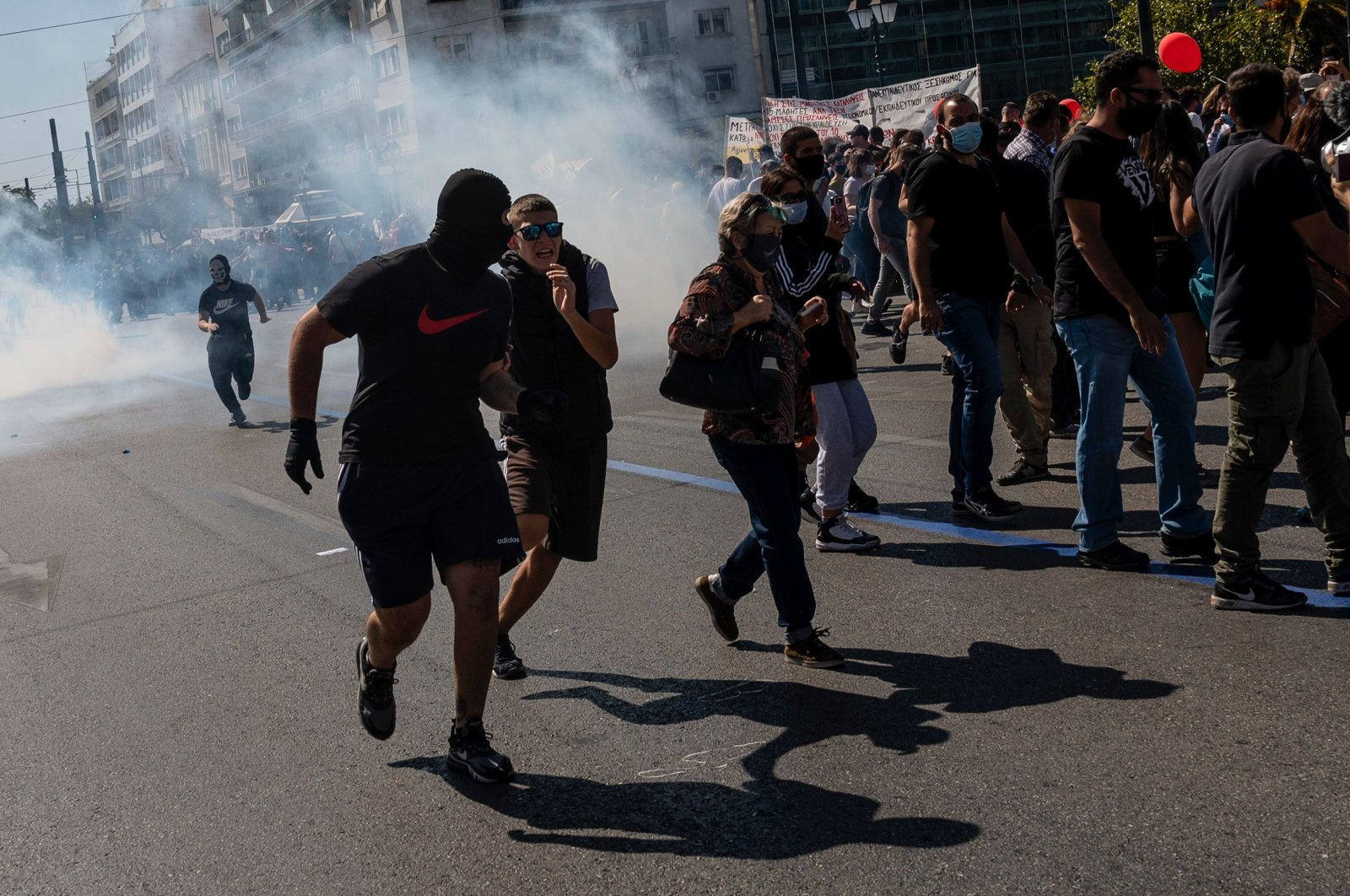 Protesters run from tear gas during a demonstration against the risks of the coronavirus in schools, in Athens, Greece, Oct. 1, 2020. (AFP Photo)
