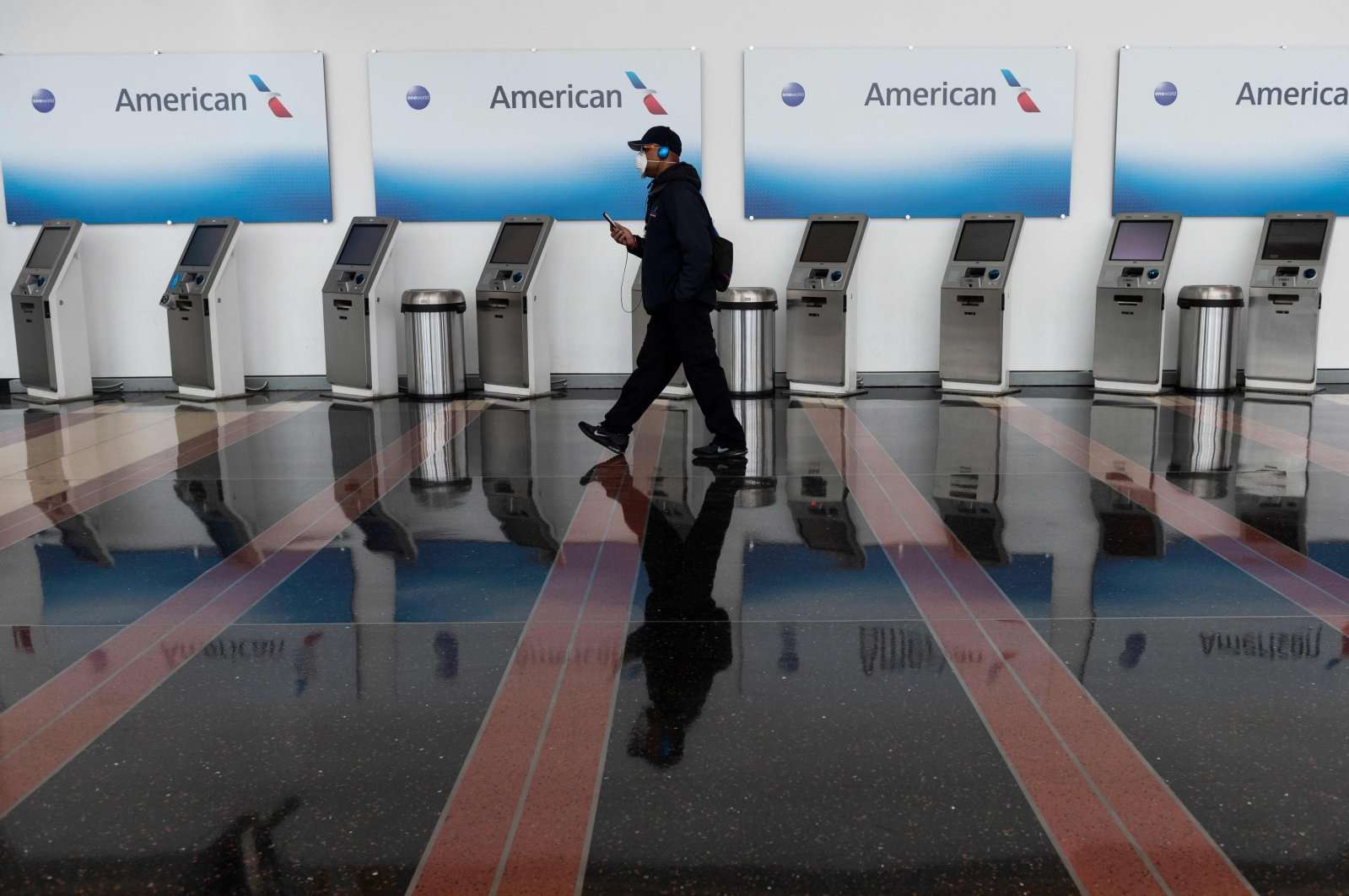 A passenger walks past empty American Airlines check-in terminals at Ronald Reagan Washington National Airport in Arlington, Virginia, the U.S., May 12, 2020. (AFP Photo)