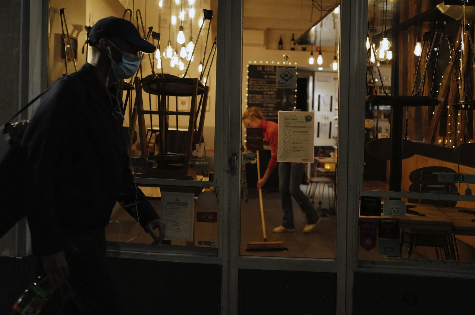 A waiter wipes to close a bar terrace in Paris, Sept. 28, 2020. (AP Photo)