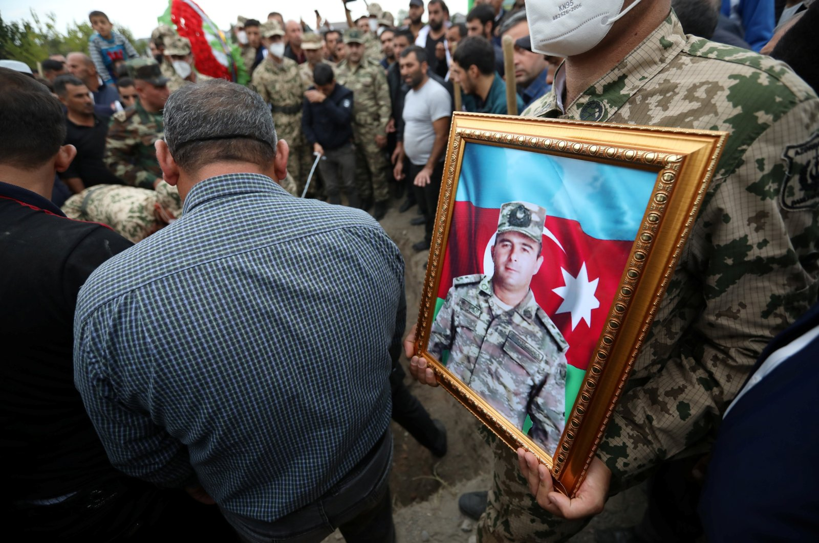 A servicemen holds a portrait of Colonel Lieutenant Makhman Ganbarov, who was killed during the fighting in Armenia-occupied Nagorno-Karabakh region, during a funeral in the city of Barda, Azerbaijan Oct. 1, 2020. (Reuters Photo)