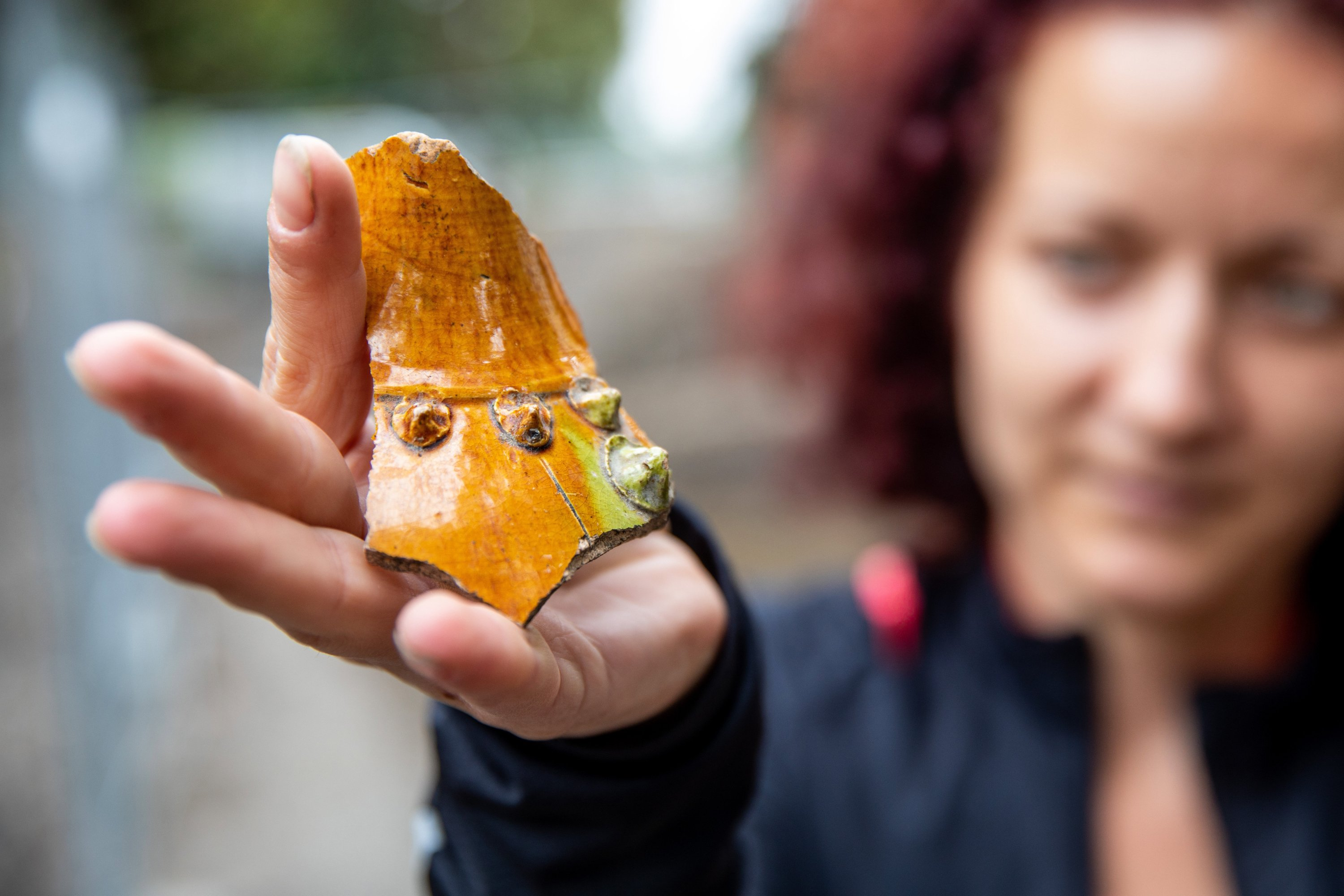 A woman holds up a fragment of pottery found at the site of an Ottoman-era tannery in Szeged, Hungary, Oct. 1, 2020. (AA Photo)