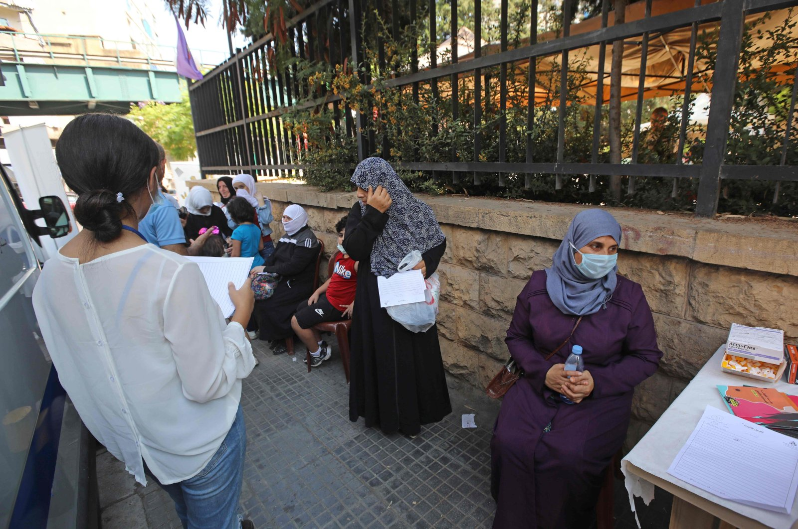 Women wait for their turn outside a mobile clinic supported by the United Nations Population Fund (UNFPA), offering free ultrasounds and tests before referring women to other health centers, in Beirut's Basta neighborhood, Lebanon, Sept. 18, 2020. (AFP Photo)